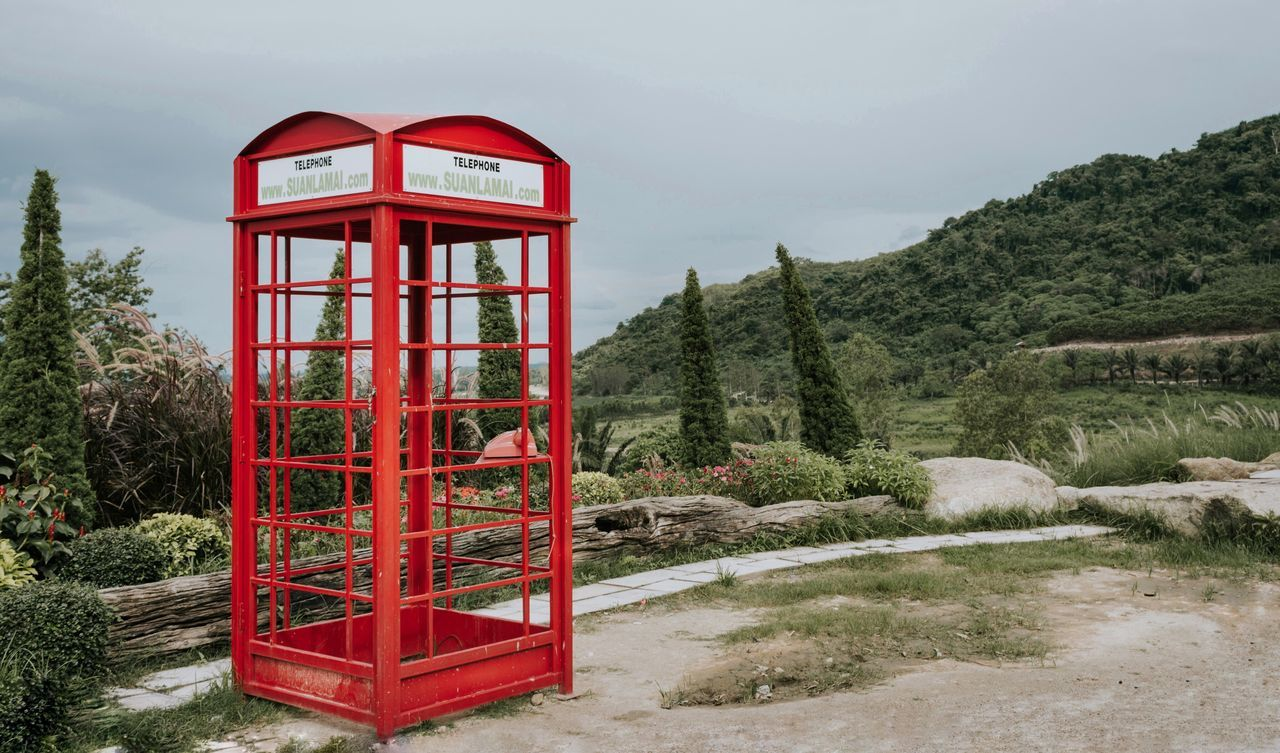 red, communication, telephone booth, tree, day, no people, connection, pay phone, sky, landscape, field, nature, outdoors, architecture, built structure, cold temperature, growth, snow, beauty in nature