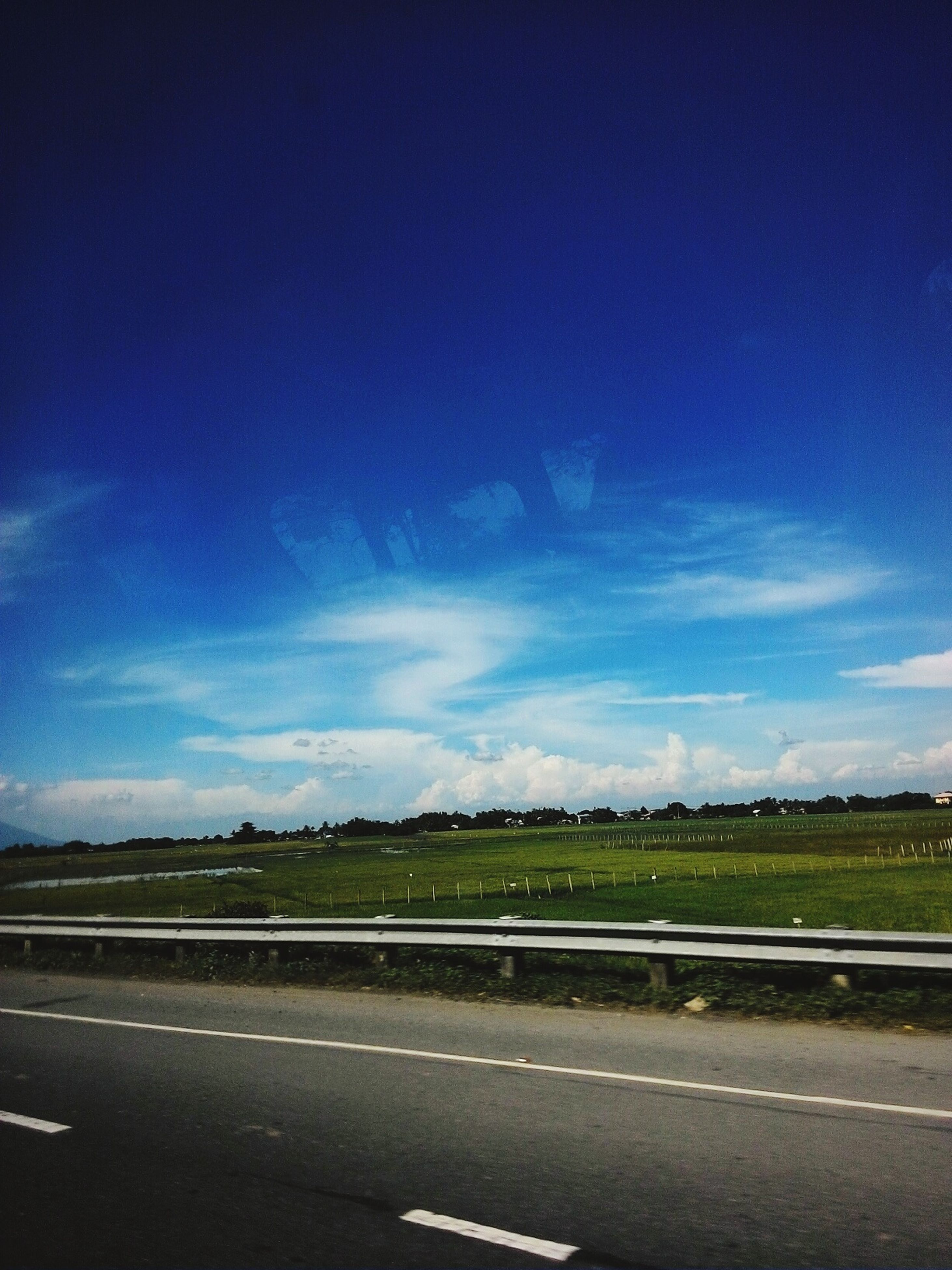 road, landscape, blue, sky, road marking, transportation, tranquil scene, tranquility, empty, scenics, dividing line, cloud, empty road, field, the way forward, country road, day, cloud - sky, solitude, outdoors, nature, non-urban scene, rural scene, countryside, long, beauty in nature, green color, vacations, tourism, crash barrier