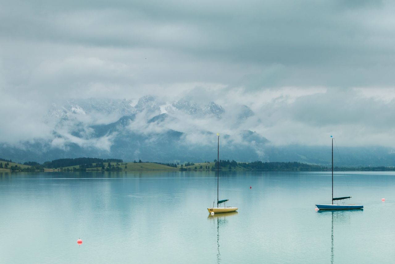 Allgäu Beauty In Nature Boat Calm Cloud Cloud - Sky Cloudy Day Forggensee Idyllic Lake Mountain Nature No People Outdoors Sailboat Tranquil Scene Tranquility Water Weather