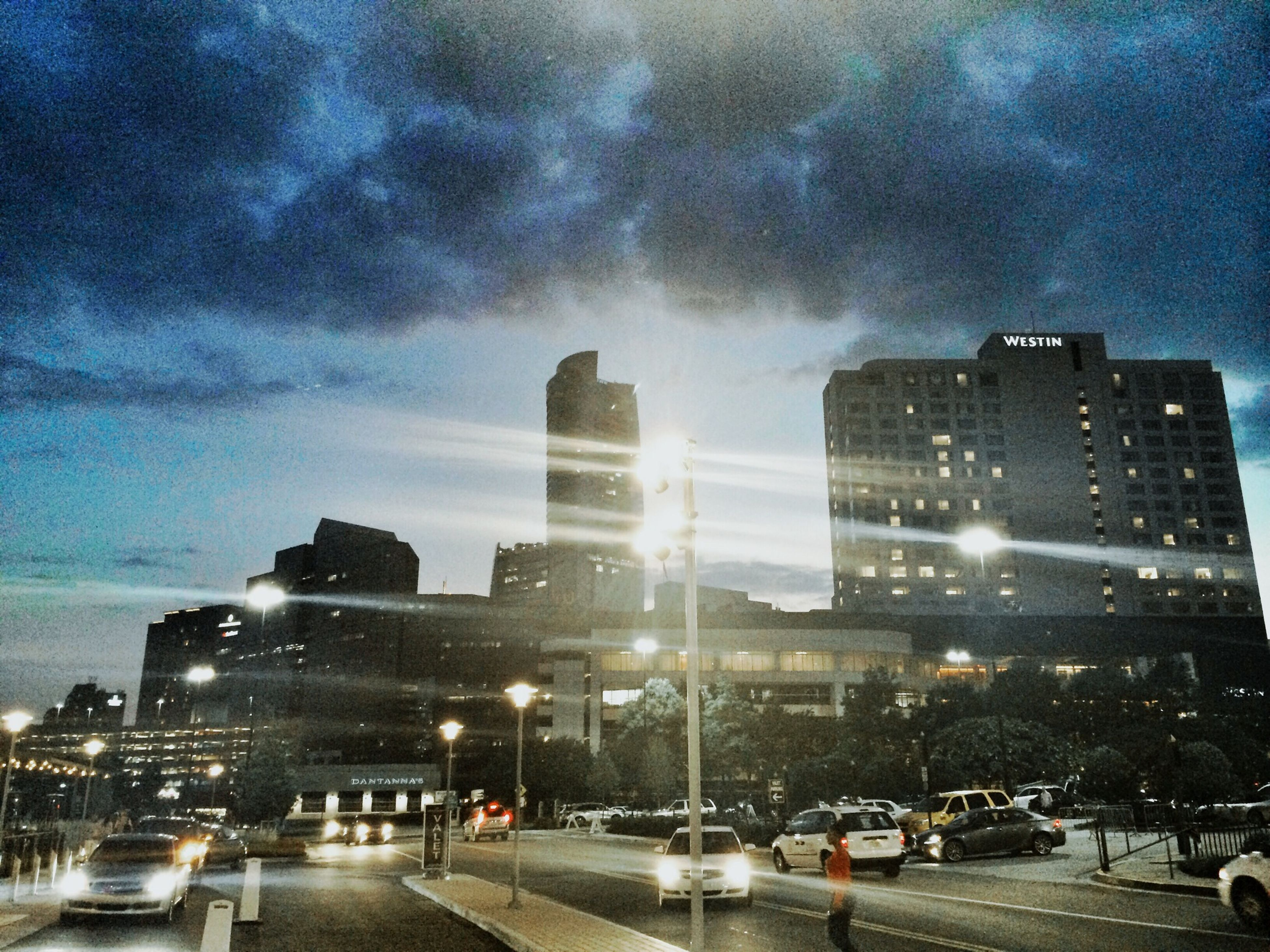 building exterior, architecture, built structure, sky, city, car, land vehicle, transportation, cloud - sky, street, road, illuminated, mode of transport, city life, cloudy, night, cityscape, city street, street light, cloud
