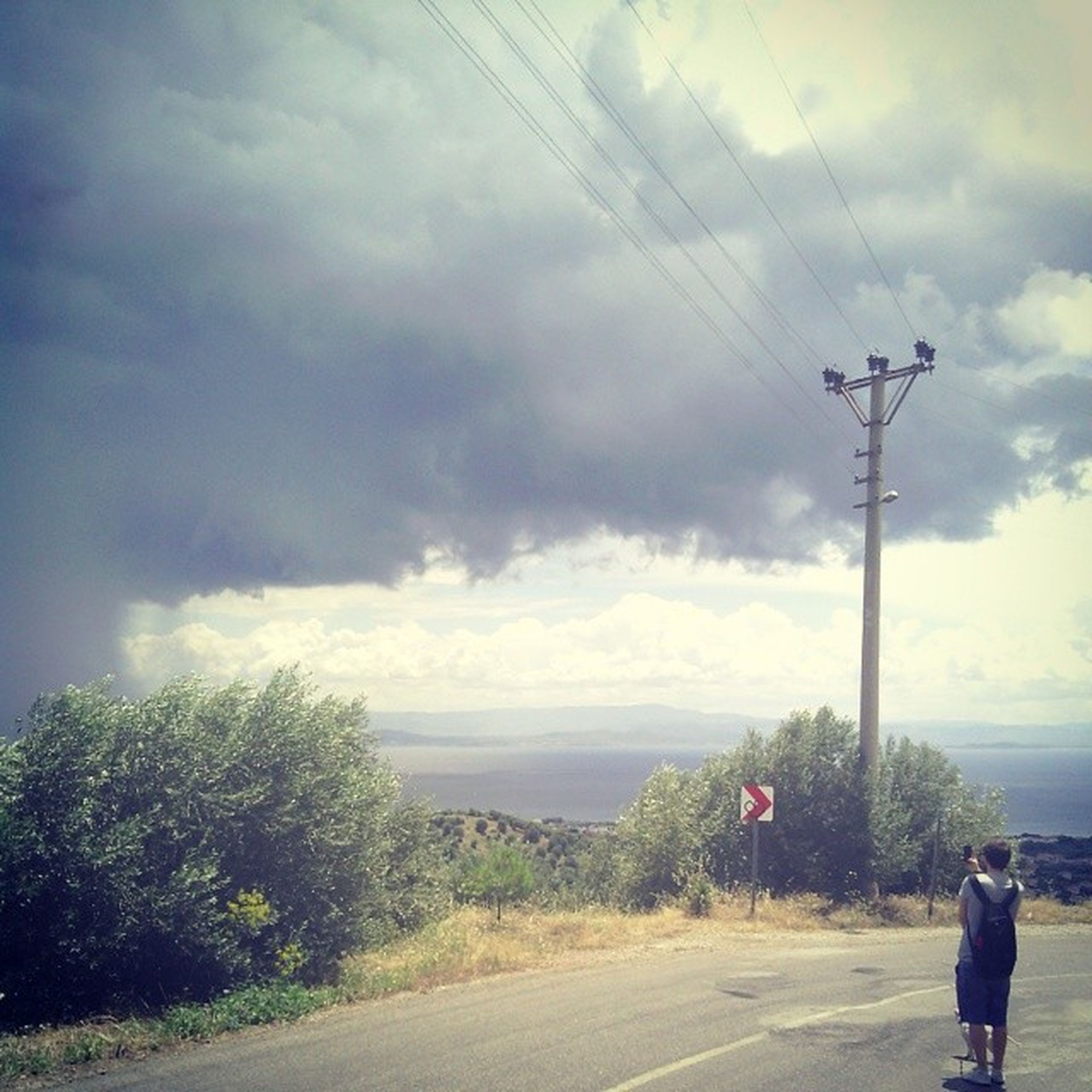 sky, cloud - sky, lifestyles, leisure activity, men, horizon over water, cloudy, sea, rear view, road, water, full length, cloud, transportation, walking, person, nature, tree