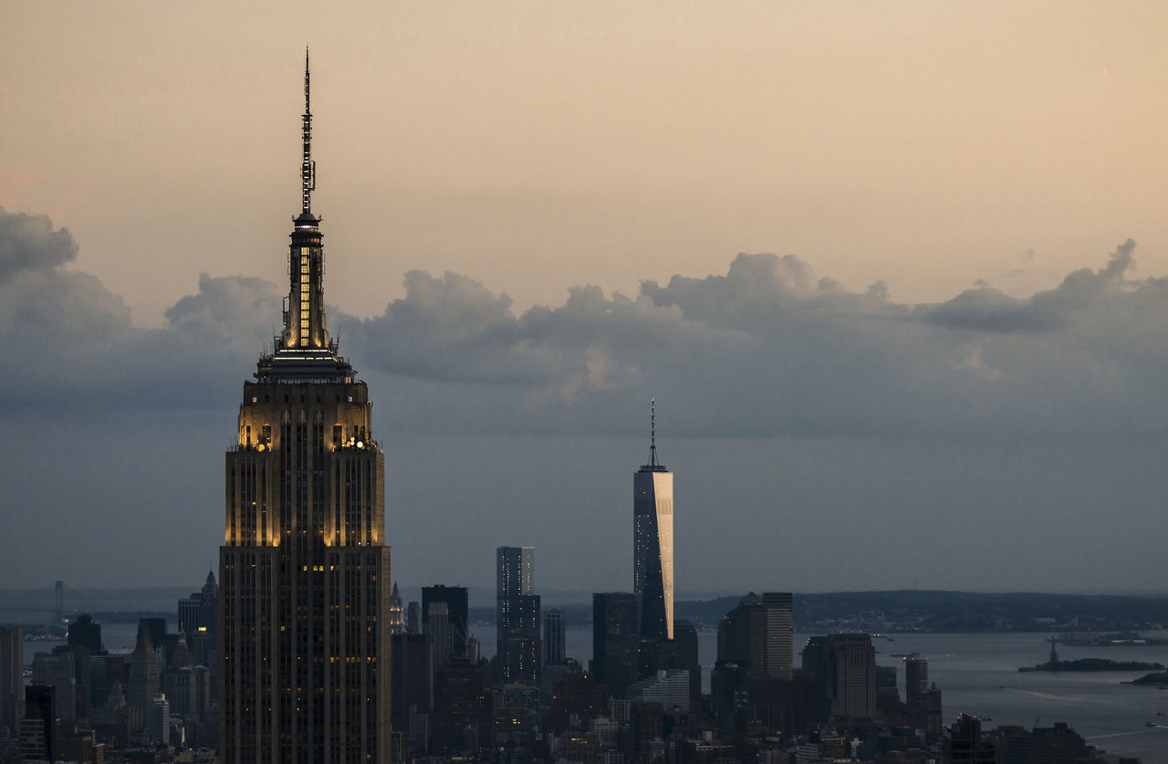 Illuminated Empire State Building By One World Trade Center In City Against Sky During Sunset