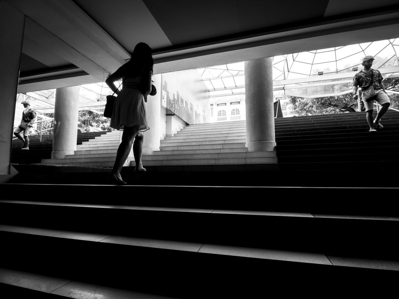 Woman walking up the steps from underground as a man walks down B&w B&w Street Photography Black And White Blackandwhite City City Life Going Up Low Angle View Railing Rear View Silhouette Stairs Steps Street Streetphotography Urban Urbanphotography Walking Woman