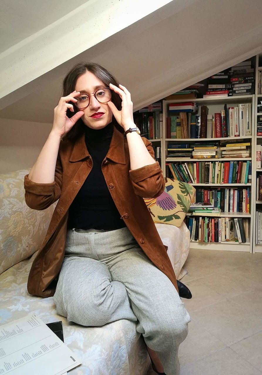 front view, book, bookshelf, casual clothing, smiling, one person, real people, using phone, mobile phone, indoors, portrait, leisure activity, young women, home interior, wireless technology, looking at camera, happiness, young adult, lifestyles, technology, library, day, people