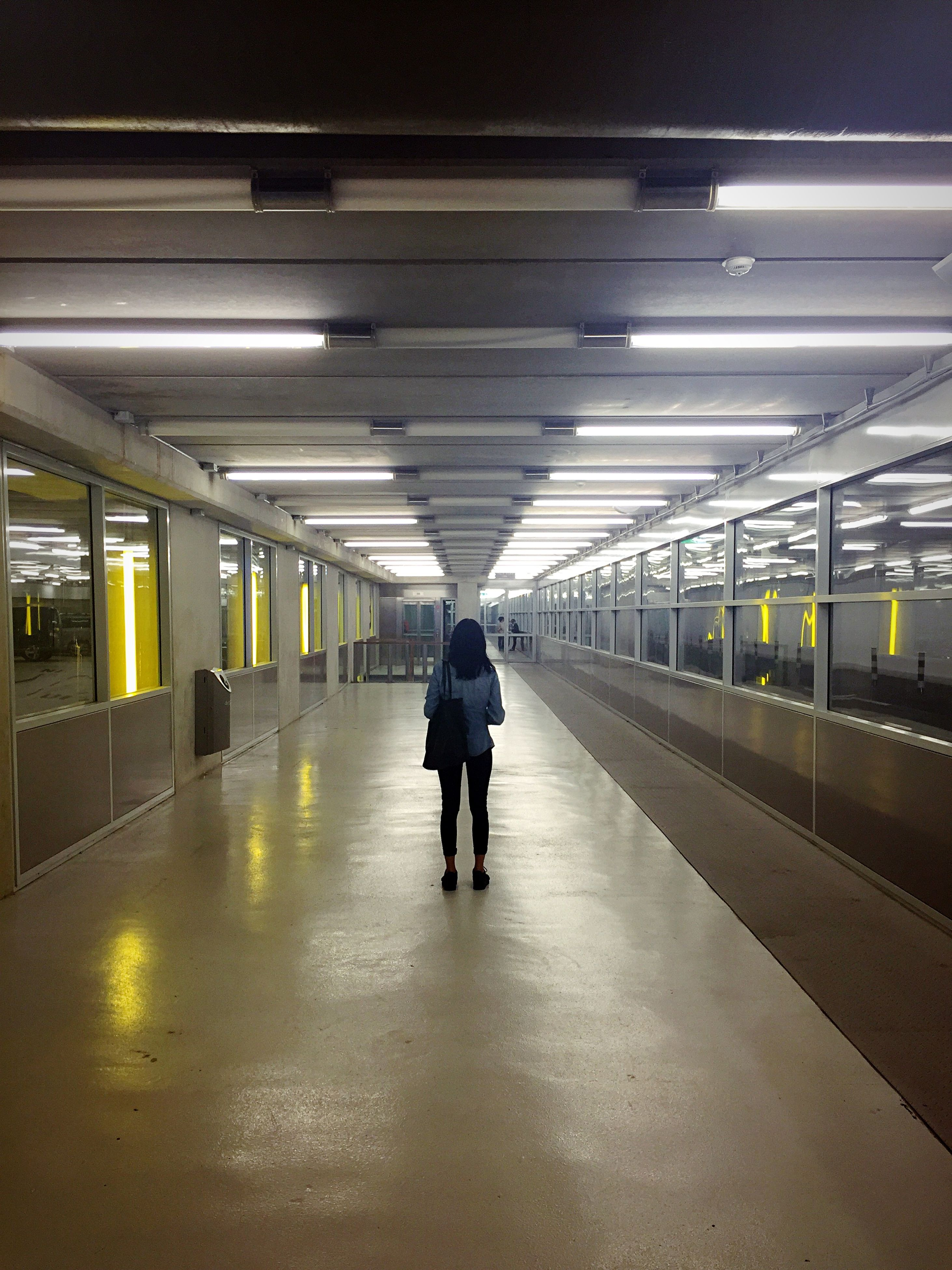 indoors, full length, walking, ceiling, illuminated, rear view, lifestyles, men, architecture, built structure, transportation, the way forward, railroad station platform, tunnel, railroad station, standing, subway, person