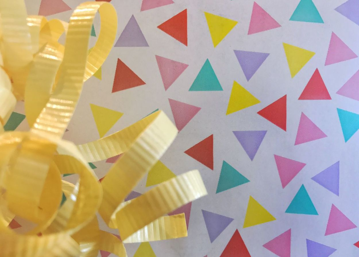 Wrapped gift. Multi Colored Wrapped Gift Yellow Ribbon Full Frame Close-up Horizontal Birthday Gift Celebration Party Present Birthday Gift Wrapping Paper Yellow Bow