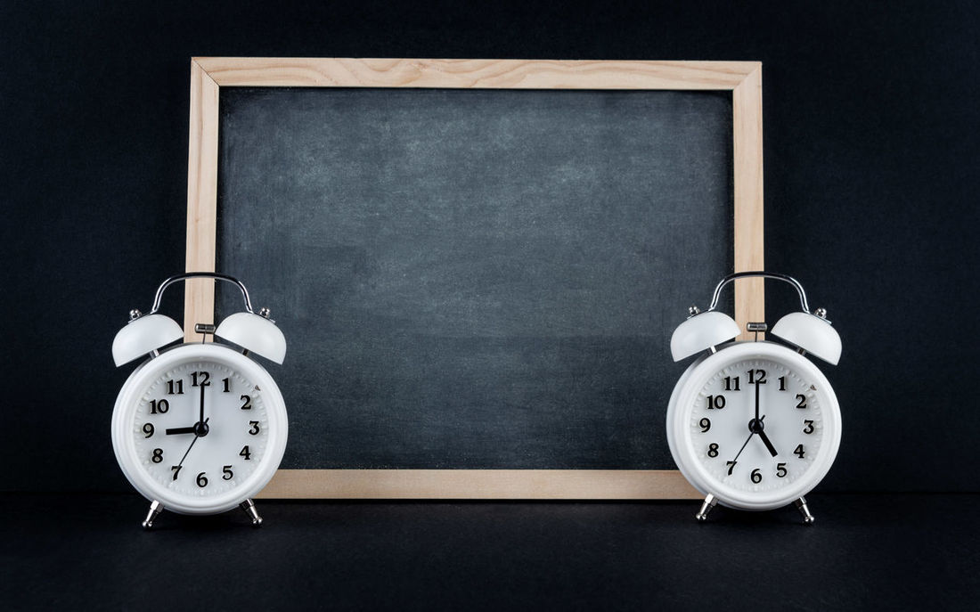 Two vintage alarm clocks showing 9 and 5 o'clock with empty chalkboard on black background. Nine to five corporate working hours concept. 9 To 5 Alarm Clock Black Background Black Color Blackboard  Clock Close-up Concept Corporate Corporate Job Day Indoors  Job No People Time