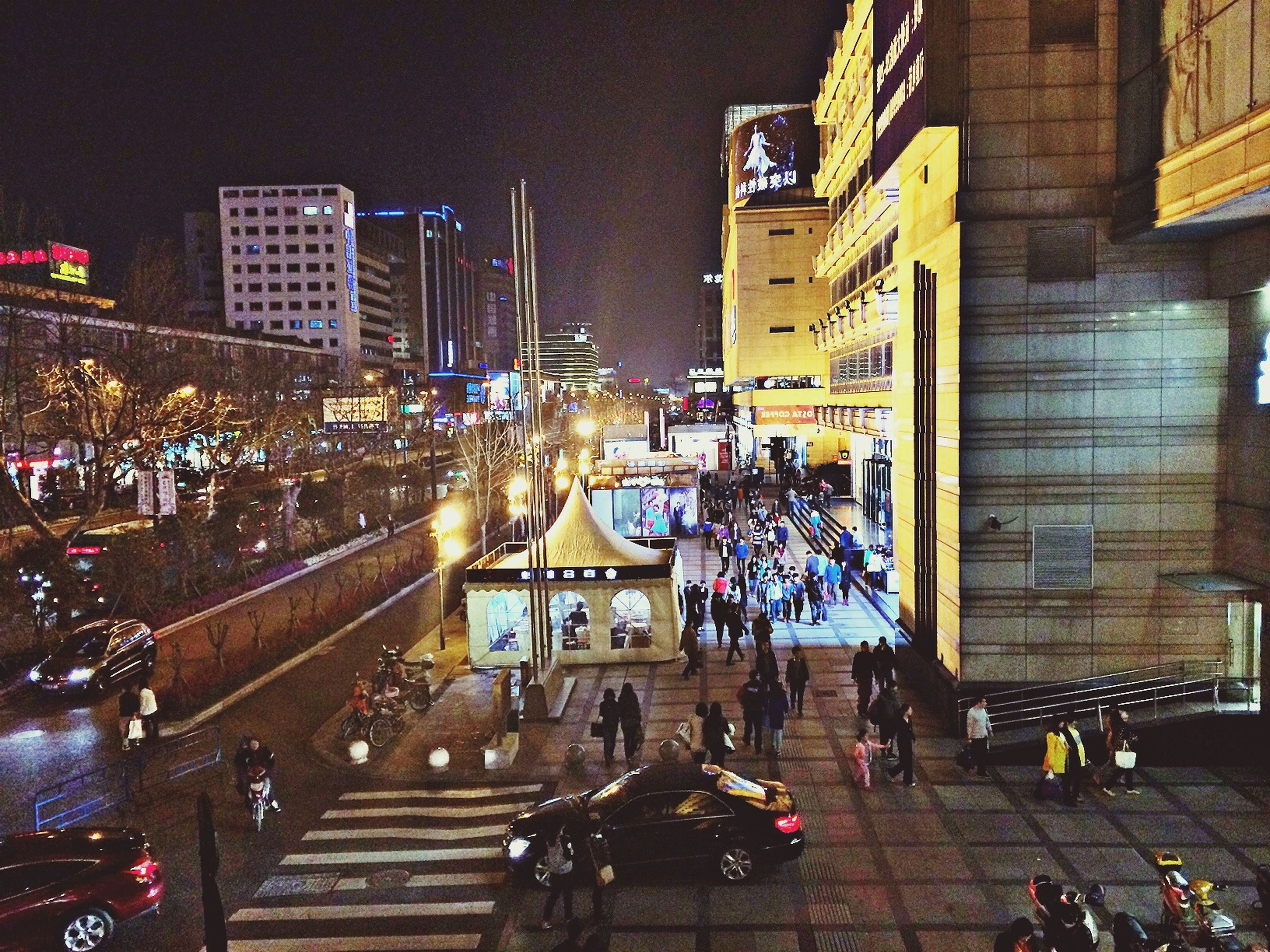 building exterior, illuminated, architecture, built structure, night, city, street, city life, city street, street light, large group of people, lighting equipment, building, text, road, outdoors, transportation, men, zebra crossing