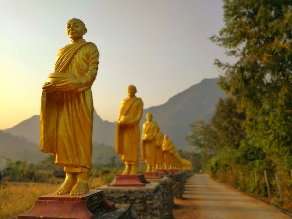 Statues of buddhist monks along the road to temple. Light Shadow Tree Mountain Art Building Beatiful City Road Countryside Rural Thailand Color Village Belive Sacred Yellow Buddha Temple Monks Statue