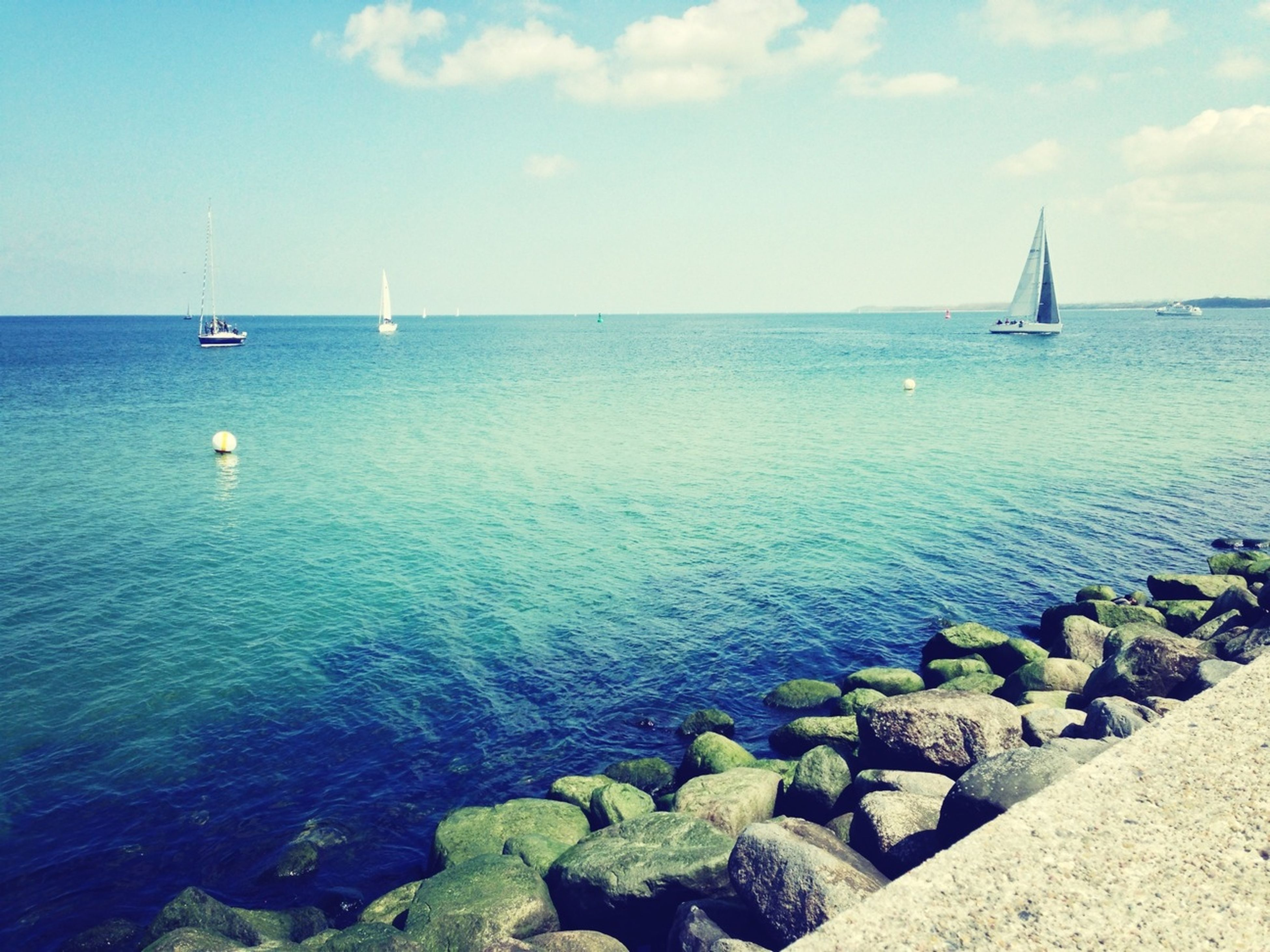 sea, water, horizon over water, transportation, nautical vessel, mode of transport, tranquil scene, tranquility, scenics, sky, beauty in nature, blue, boat, nature, rock - object, seascape, idyllic, day, travel, sailboat