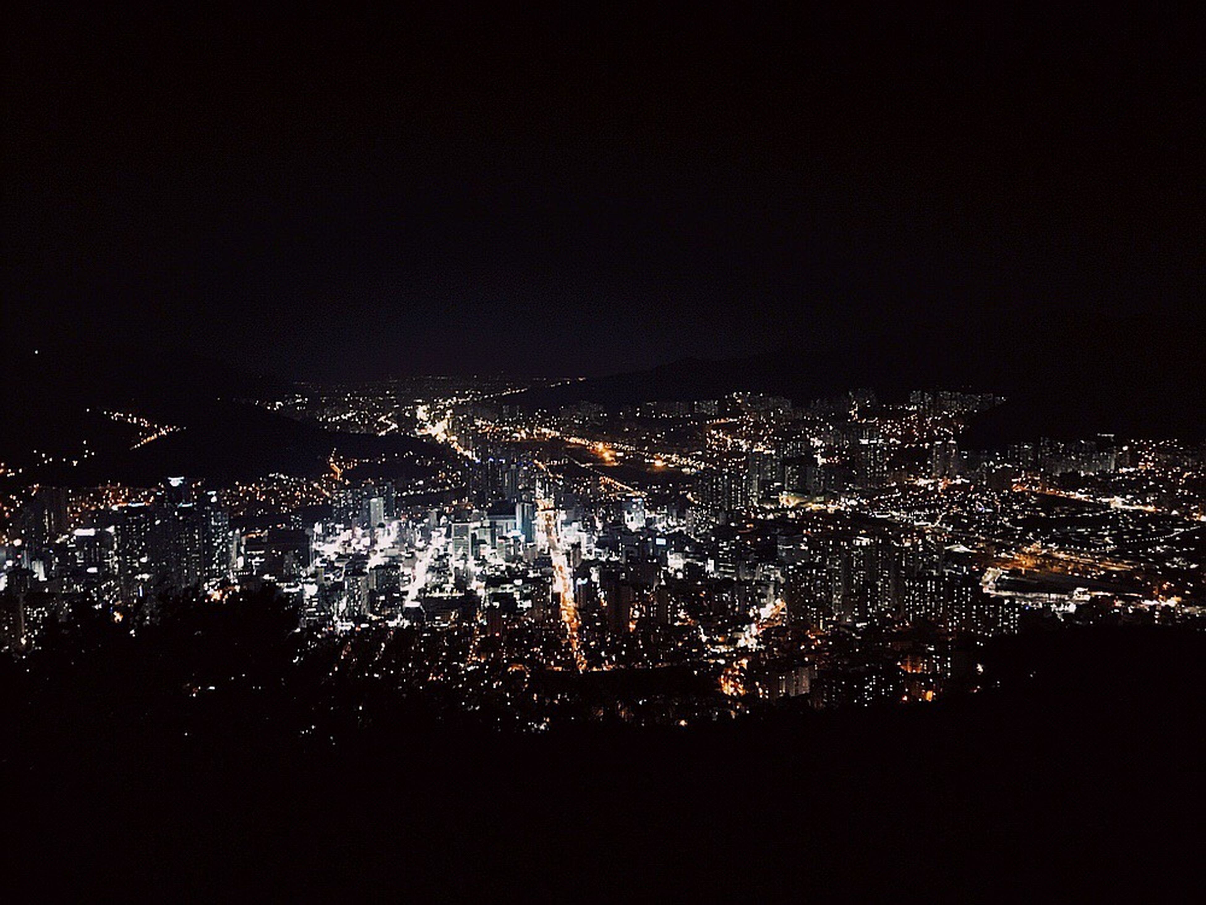 illuminated, night, cityscape, city, crowded, building exterior, architecture, built structure, high angle view, aerial view, copy space, residential district, dark, sky, city life, skyscraper, clear sky, residential building, no people, residential structure