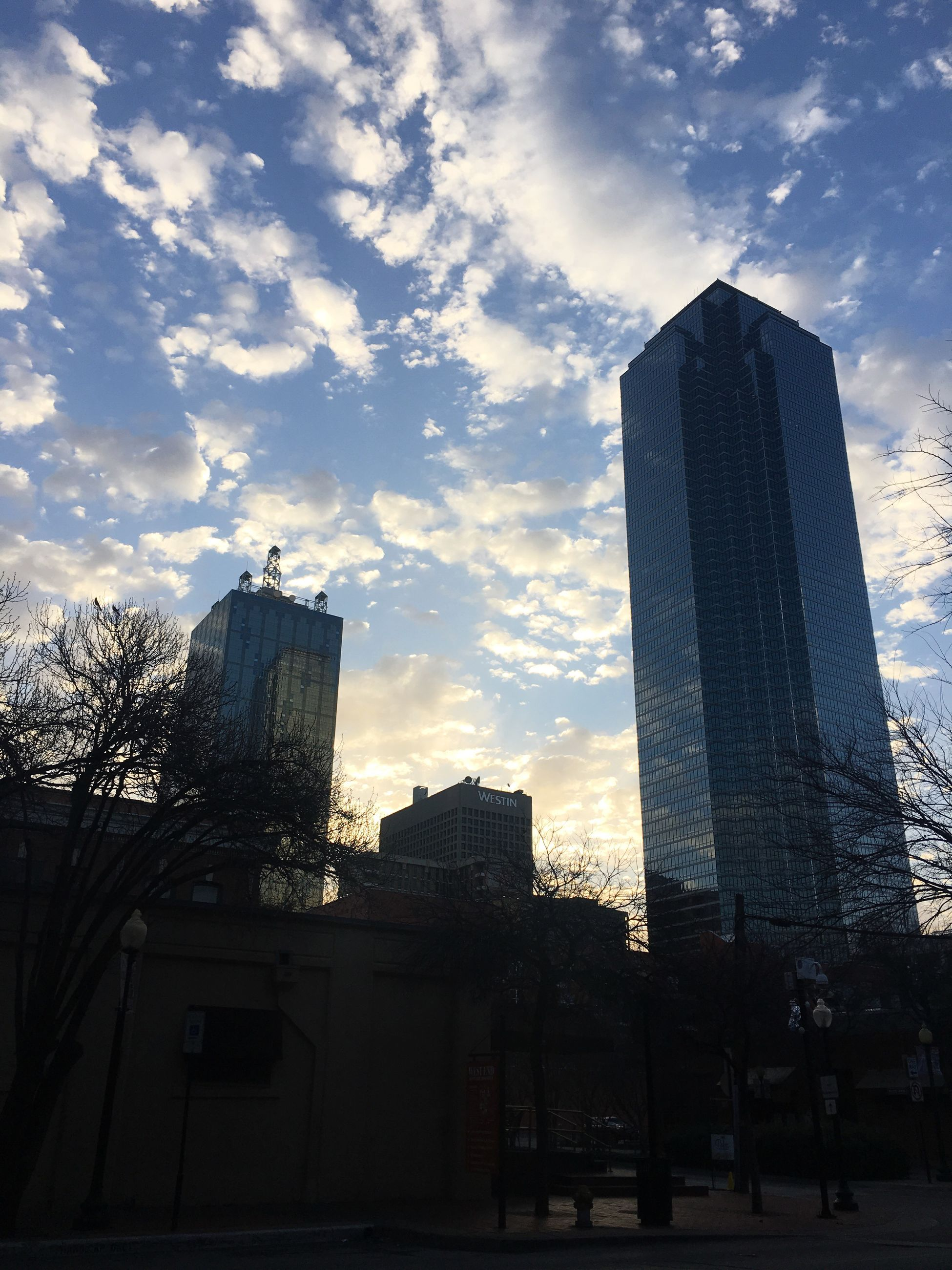 city, skyscraper, architecture, building exterior, sunset, no people, built structure, outdoors, modern, sky, low angle view, city life, cloud - sky, urban skyline, downtown district, cityscape, day