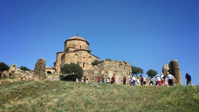Tourists walk up a hill to Jvari Monastery at Mtskheta, Georgia Georgia Caucasus Traveling Church