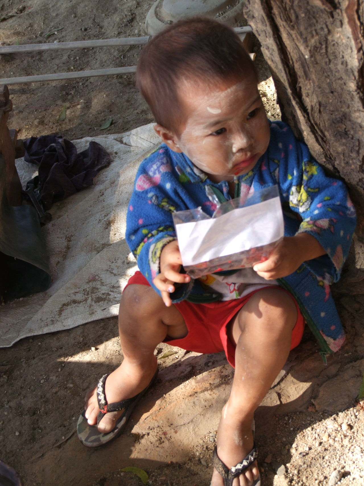 Child in Pakokku Village Boy Boy Portrait Buddhist Culture Child Composition Full Frame Holding Paper Looking Away From Camera Myanmar No Incidental People One Person Outdoor Photography Pakokku Portrait Red And Blue Colour Sitting Sunlight And Shade Traditional Clothing