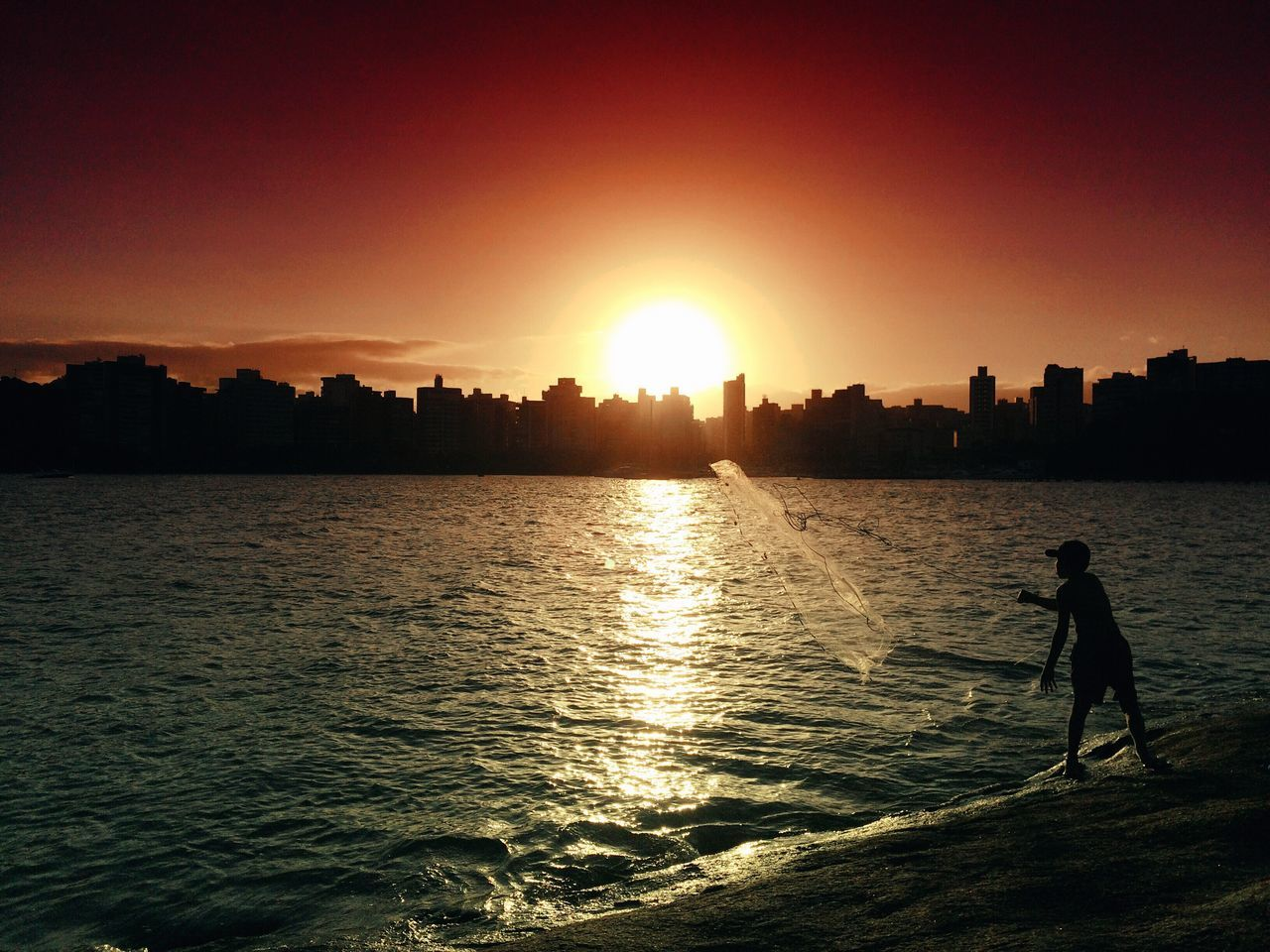Rear View Of Silhouette Boy Throwing Fishing Net In River At Sunset
