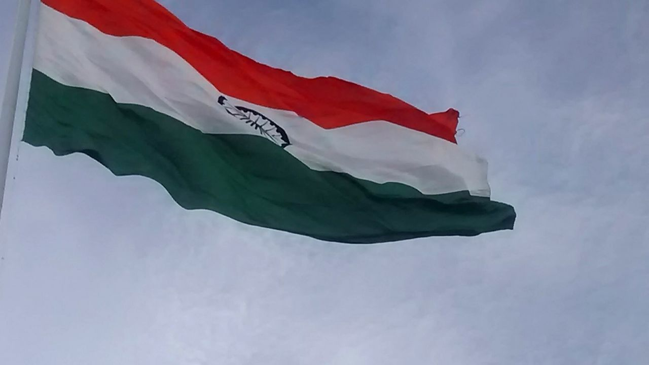 flag, patriotism, low angle view, wind, outdoors, waving, day, no people, pride, sky, cloud - sky