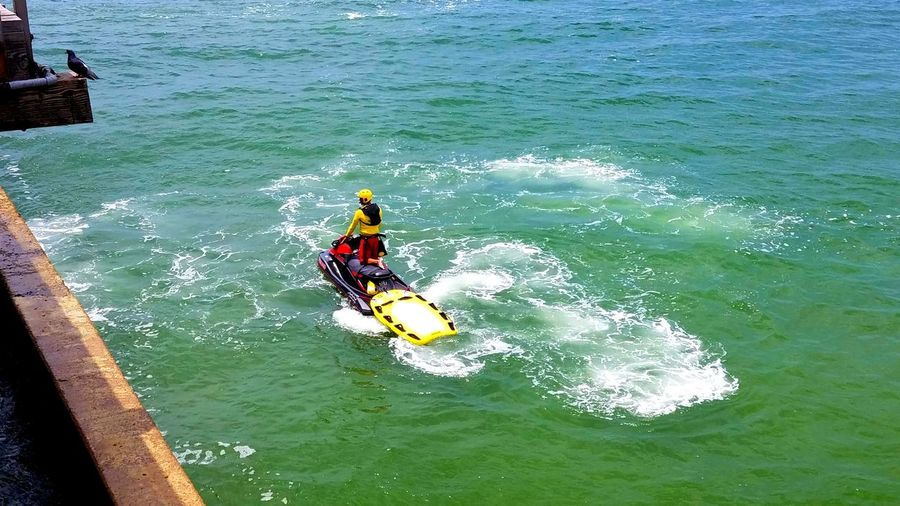 Life Guard On Duty Lifeguard  Extreme Sports Nature Lifestyles Nautical Vessel Real People High Angle View Motion Wave Water Ocean Layered Colors Swirls Rescue SpeedDramatic Activity Wave Sports Helmet Vivid Ocean Craft Yellow Background Copy Space Breathing Space