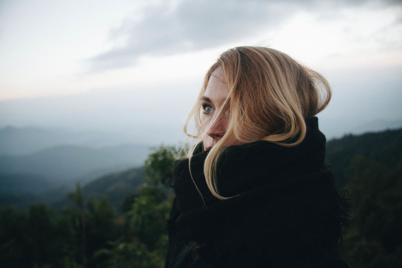Thoughtful Young Woman Standing Against Mountains