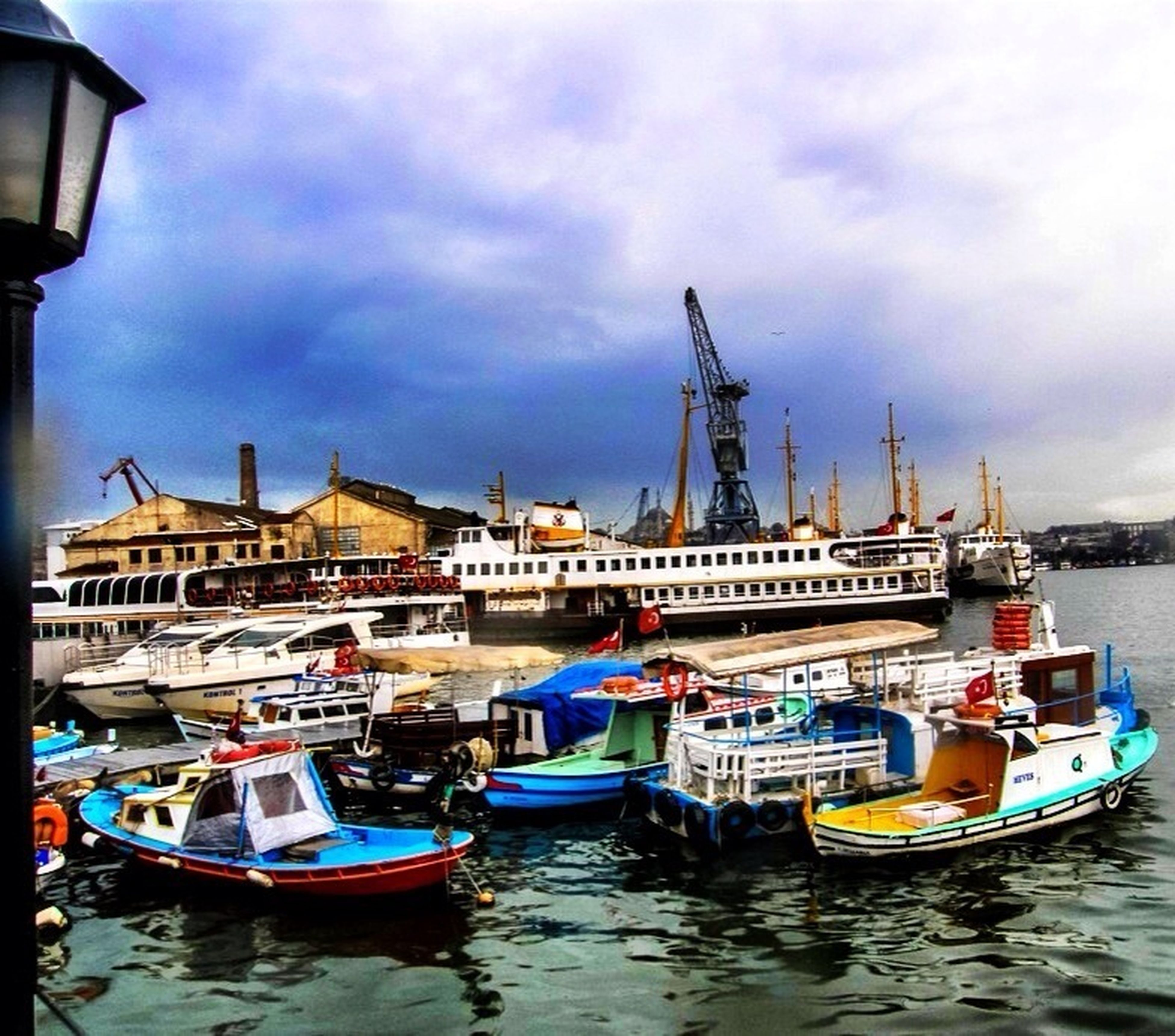 architecture, nautical vessel, building exterior, built structure, waterfront, sky, water, moored, transportation, cloud - sky, boat, mode of transport, cloud, cloudy, harbor, outdoors, day, no people, city, river
