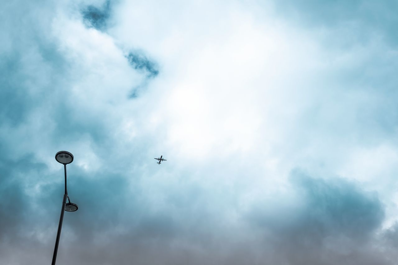 Aircraft Airplane Cloud Cloud - Sky Cloudscape Copy Space Day Flying High In The City Lookingup Low Angle View Minimalism Minimalist Minimalobsession Silhouette Sky Street Lamp Street Light Street Light Traffic Transportation Weather