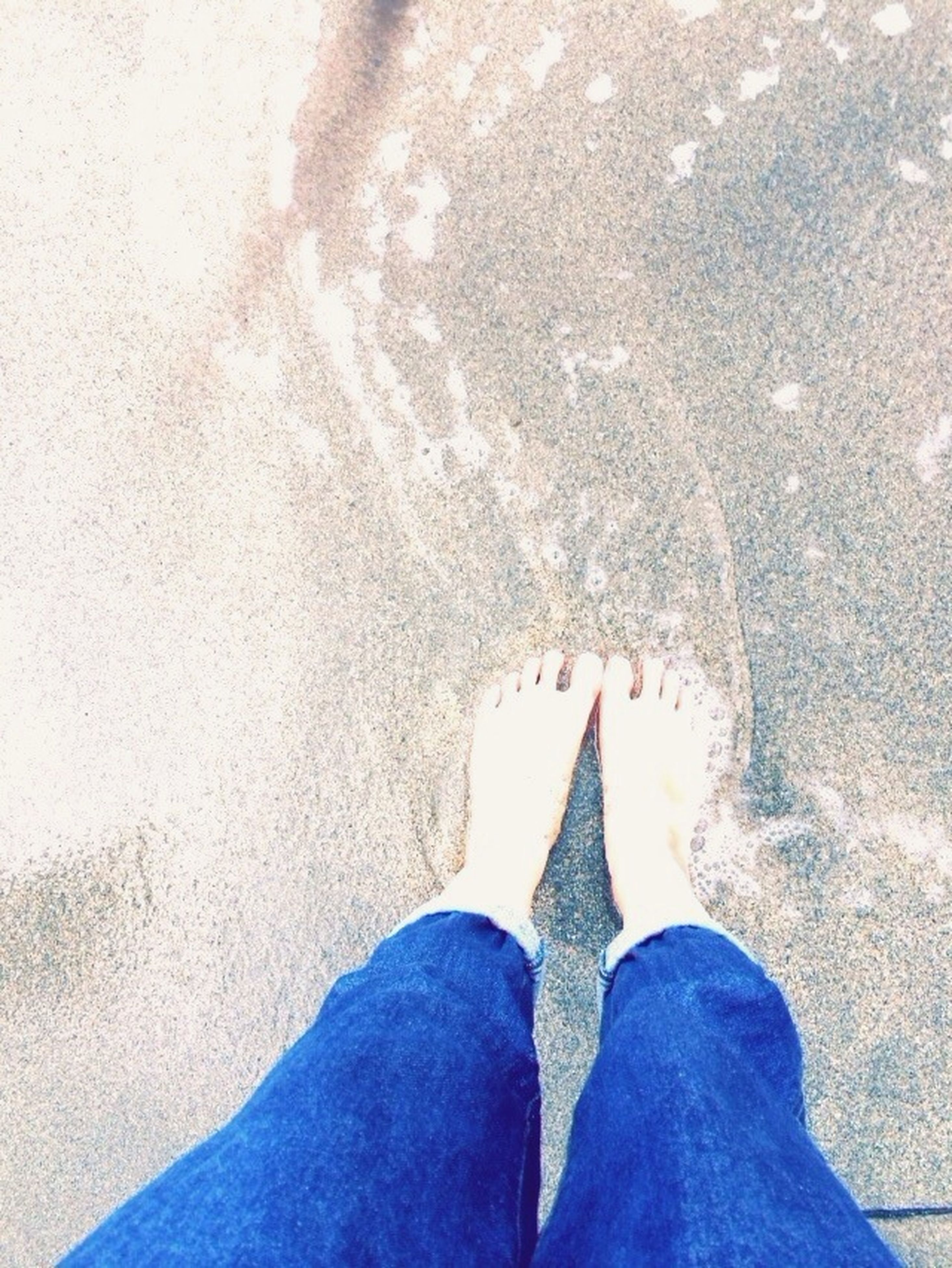 low section, person, personal perspective, shoe, standing, human foot, high angle view, lifestyles, jeans, unrecognizable person, leisure activity, close-up, men, outdoors, part of, day, sand
