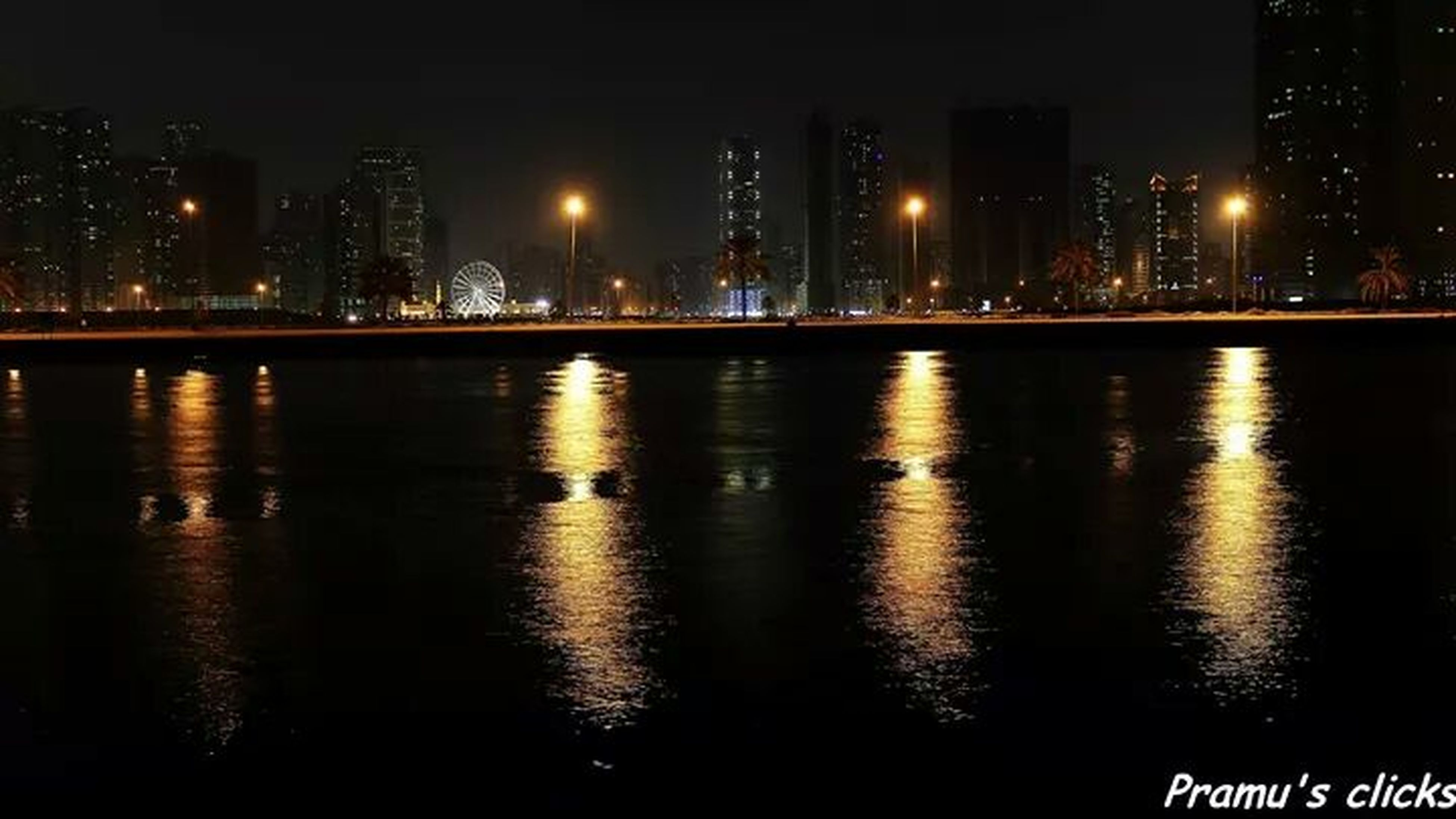 illuminated, night, water, city, river, architecture, building exterior, waterfront, built structure, reflection, cityscape, connection, sky, sea, bridge - man made structure, skyscraper, urban skyline, no people, outdoors, transportation