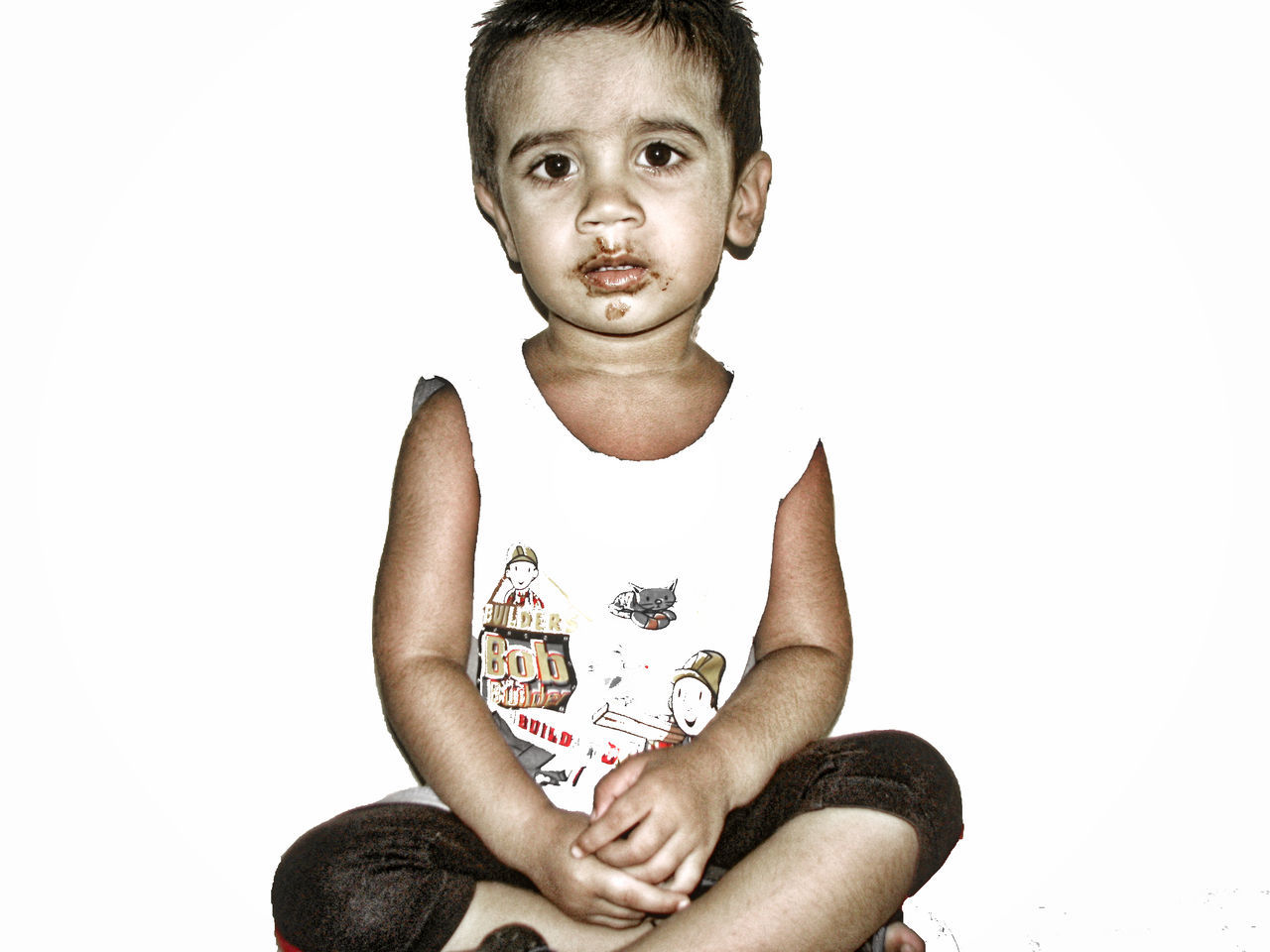 Portrait Of Cute Boy With Messy Mouth Sitting Against White Background