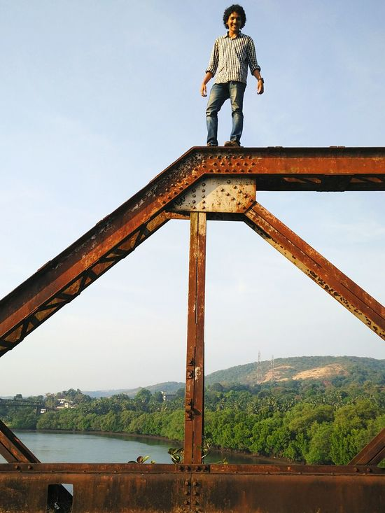 Thrillseeker. Thrill Outdoors Boy Thrillseeker Thrill Seeker Dangerous Dangerous Beings Daring Dare To Be Different Dare To Climb Top Of The World Bridge Truss Bridge Truss Goa Rusted Rusted Iron Structure Borim Bridge Borim Old Borim Bridge Ancient Historical Historical Site Goa India Haunted Places