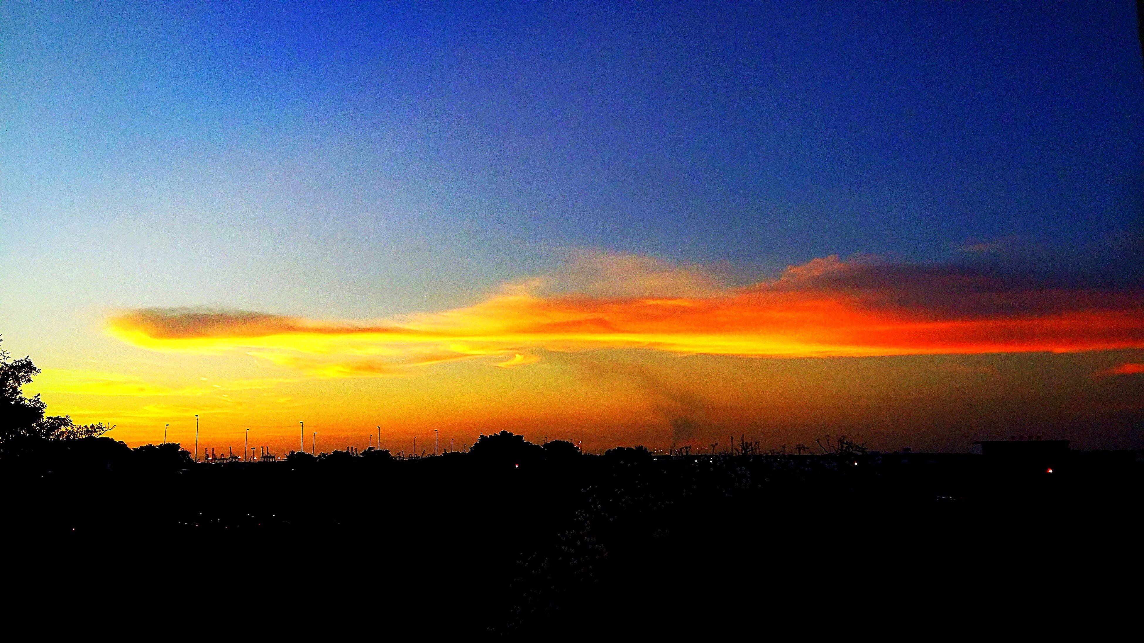 sunset, silhouette, orange color, scenics, sky, tranquil scene, beauty in nature, cloud - sky, tranquility, nature, calm, outline, cloud, blue, outdoors, majestic, moody sky, no people, dramatic sky, cloudy, atmospheric mood