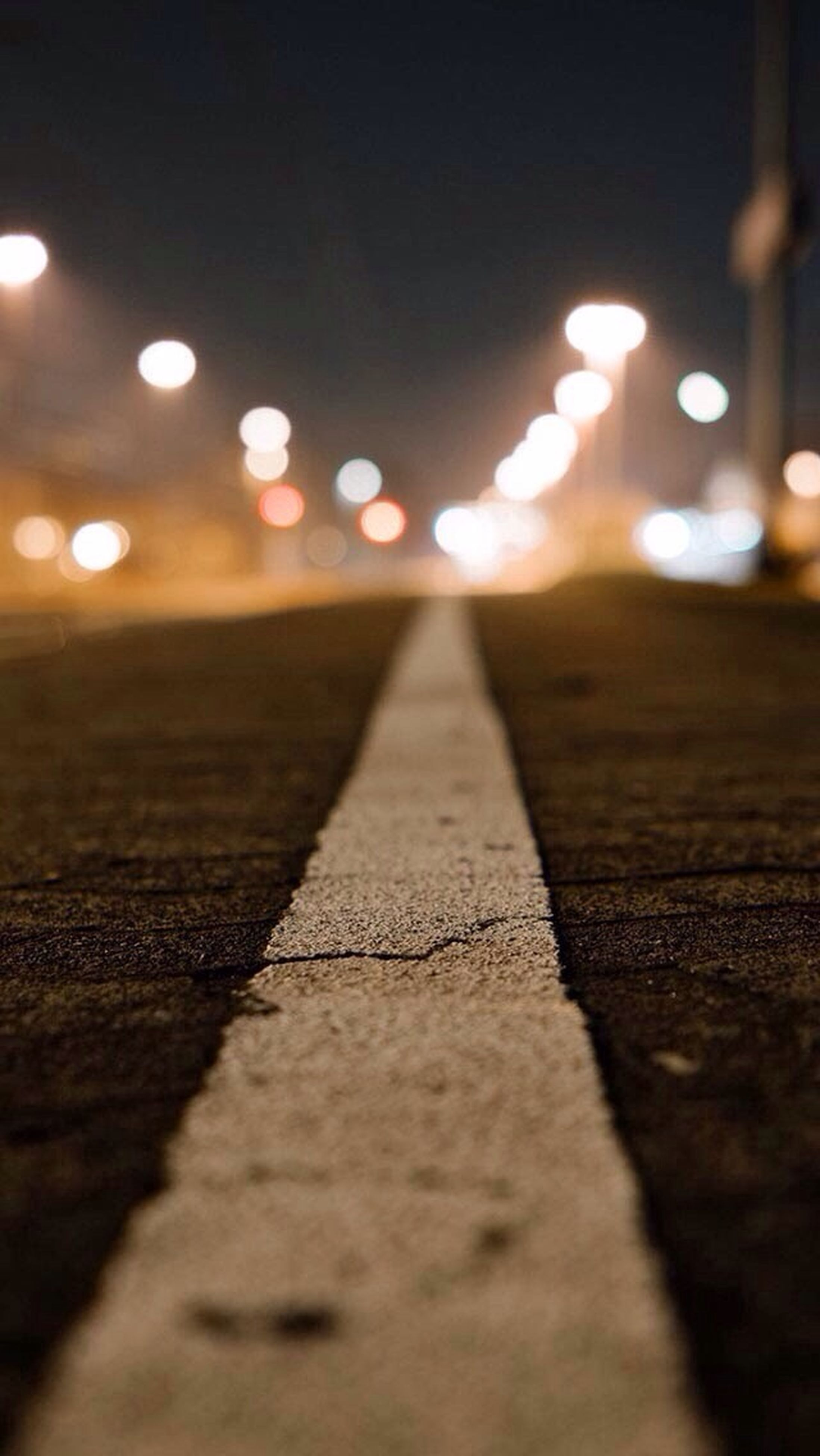 surface level, defocused, selective focus, illuminated, street, lens flare, night, road, asphalt, focus on foreground, the way forward, sunset, outdoors, wet, transportation, no people, sunlight, road marking, sky, close-up