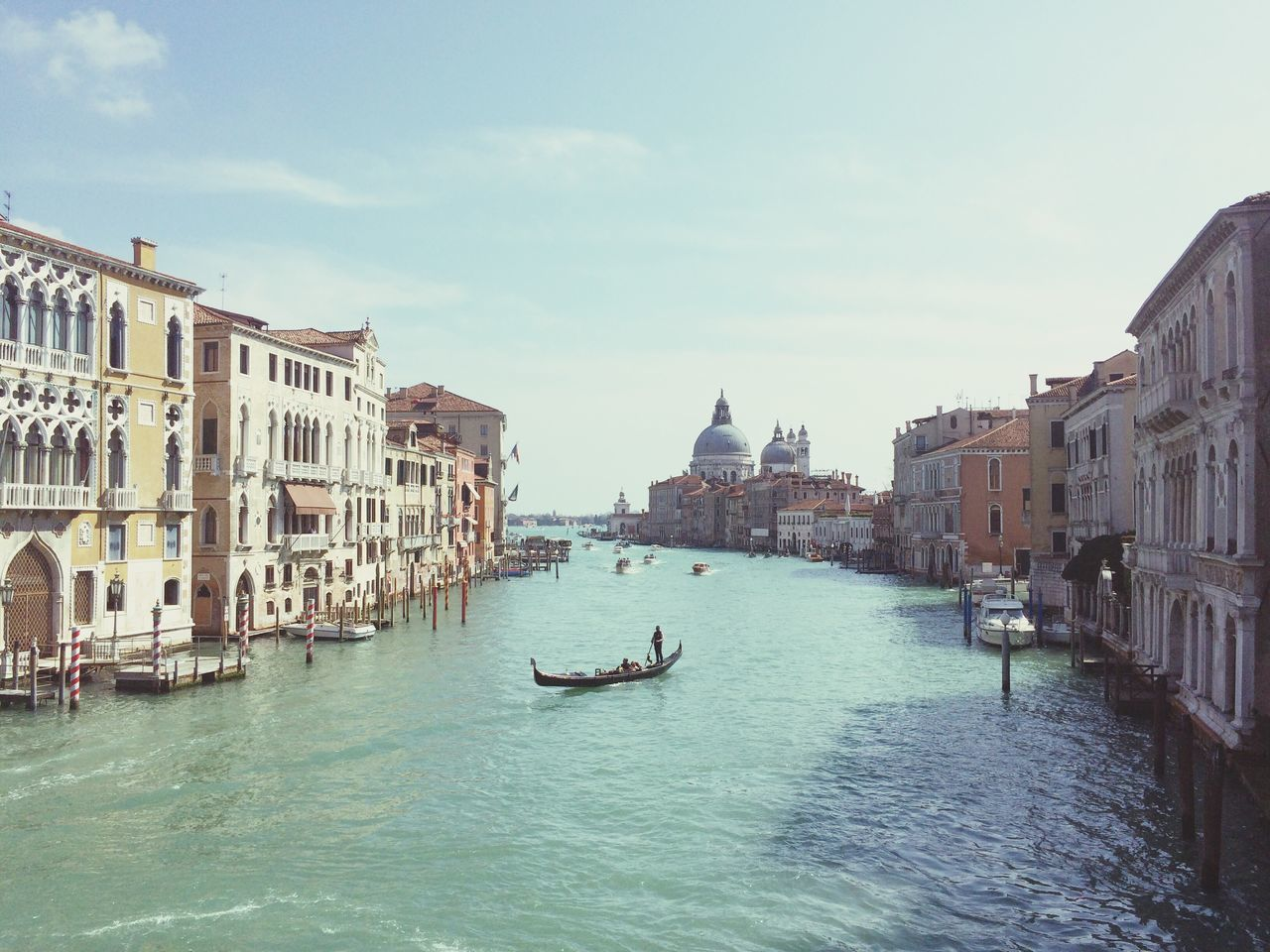 gondola - traditional boat, canal, nautical vessel, architecture, transportation, gondolier, gondola, building exterior, water, mode of transport, built structure, day, waterfront, outdoors, real people, travel destinations, oar, men, rowing, wooden post, sky, one person, people