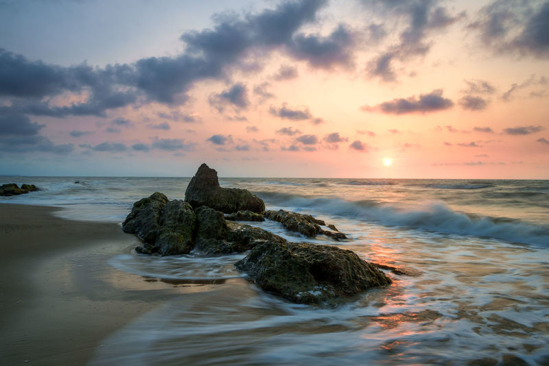 Beautiful sunset on rocky beach Beach Beautiful Nature Colorful Sky And Clouds Motion Blur Nature No People Orange Sky Outdoors Rocky Beach Sarawak Scenics Sea Seascapes Slow Shutter Sunlight Sunset Waves