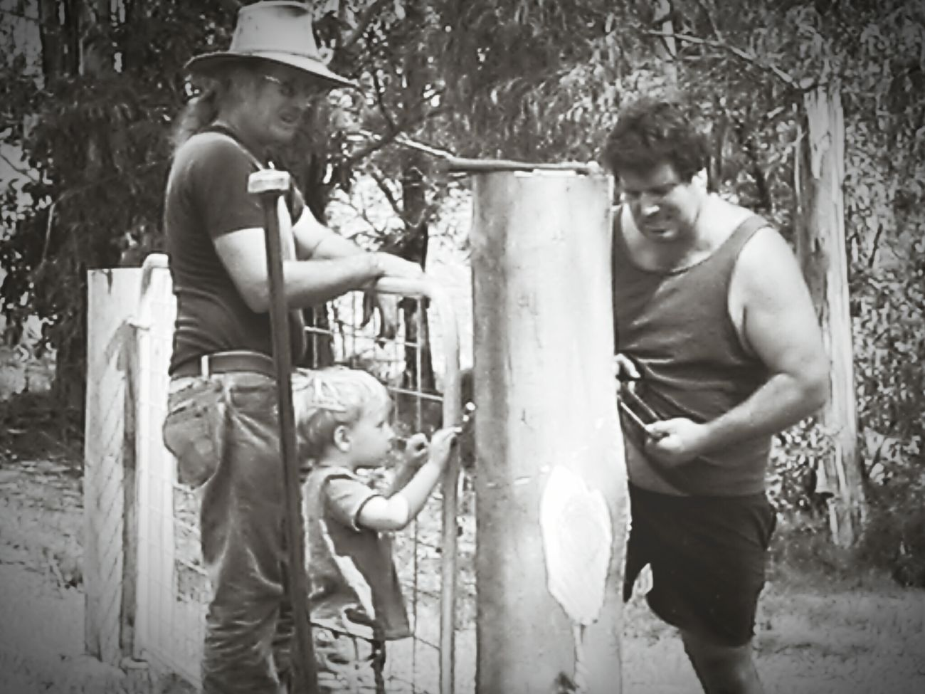 RePicture Masculinity Farming Fencing The Old Ways... Black And White Teaching The Youth  Watching Dad How Its Done Son Hand Drill Gate