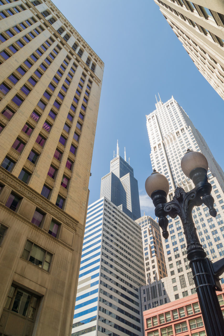 Low Angle View Of Street Light By Modern Buildings Against Clear Sky