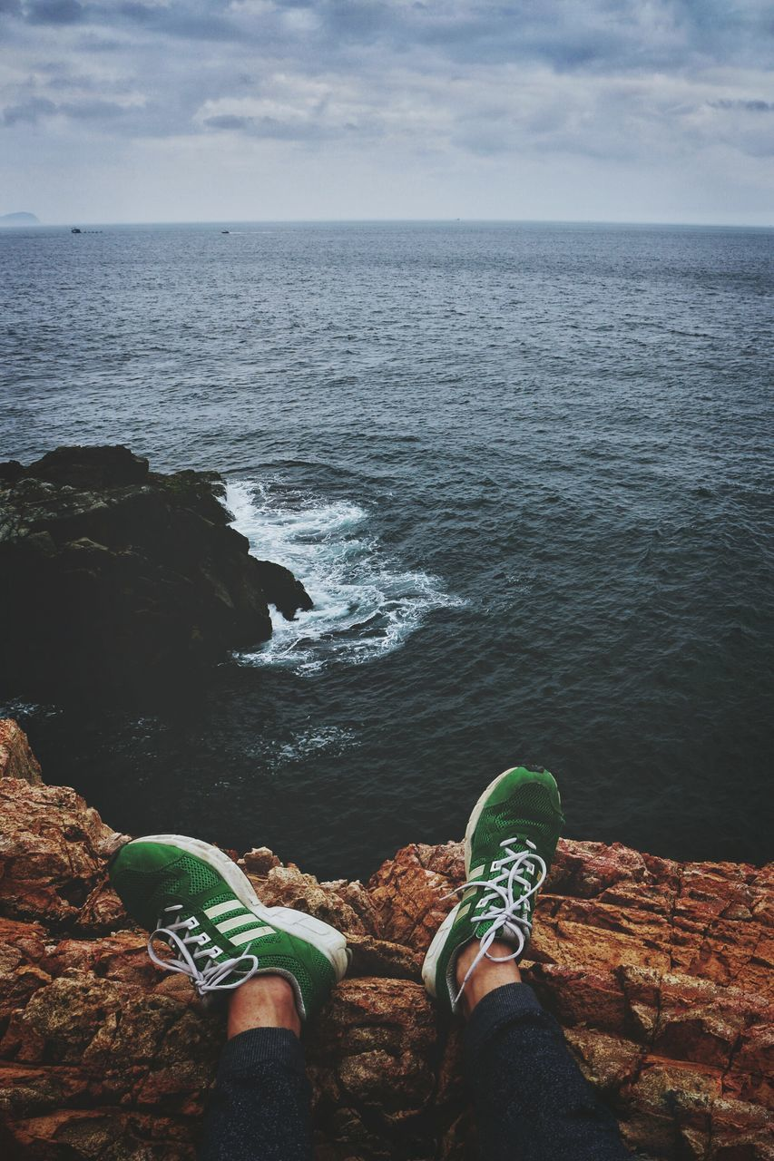 sea, horizon over water, water, low section, nature, human leg, rock - object, one person, scenics, beauty in nature, day, shoe, outdoors, tranquility, tranquil scene, cloud - sky, sky, standing, real people, men, people
