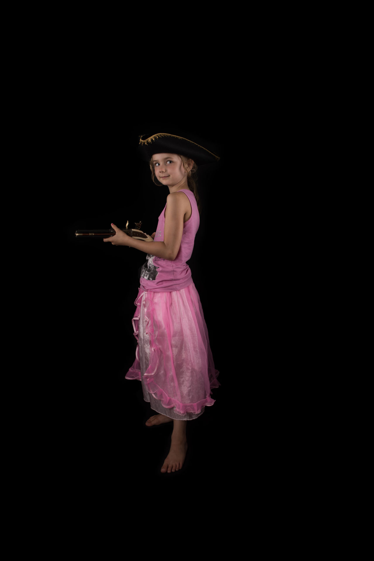 Black Background Casual Clothing Child Confidence  Front View Full Length Girl Girly Hat In Front Of Looking At Camera Person Pink Color Pirate Hat Pirates Playing Standing Studio Shot Young Adult Young Women
