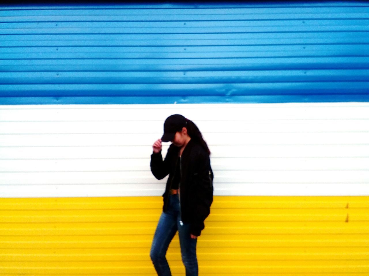 one person, young adult, real people, standing, young women, lifestyles, striped, leisure activity, yellow, front view, casual clothing, day, outdoors, blue, corrugated iron, full length, architecture, adult, people