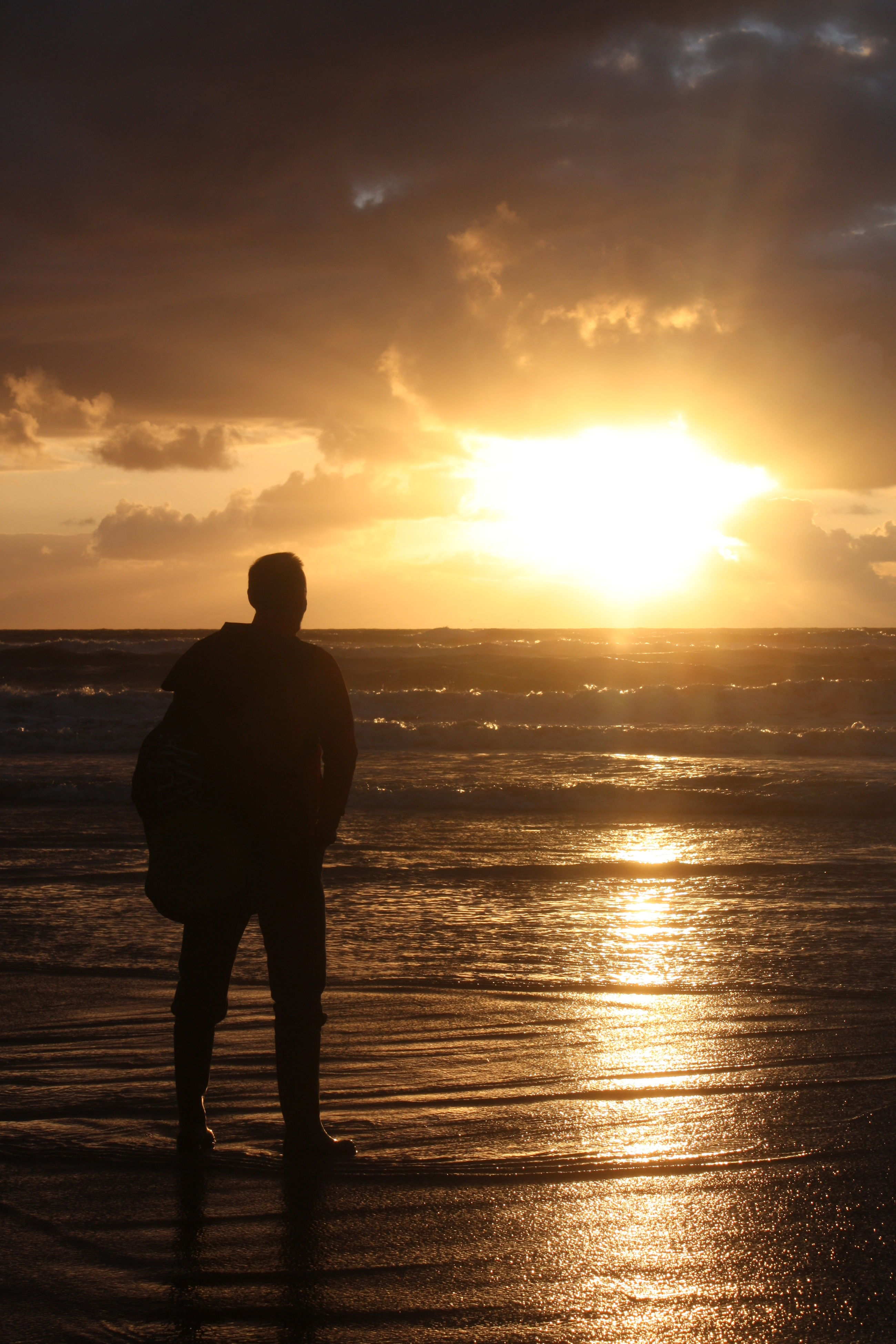 sunset, silhouette, sun, lifestyles, sky, leisure activity, standing, men, water, sea, orange color, tranquility, scenics, beauty in nature, sunlight, tranquil scene, nature, rear view