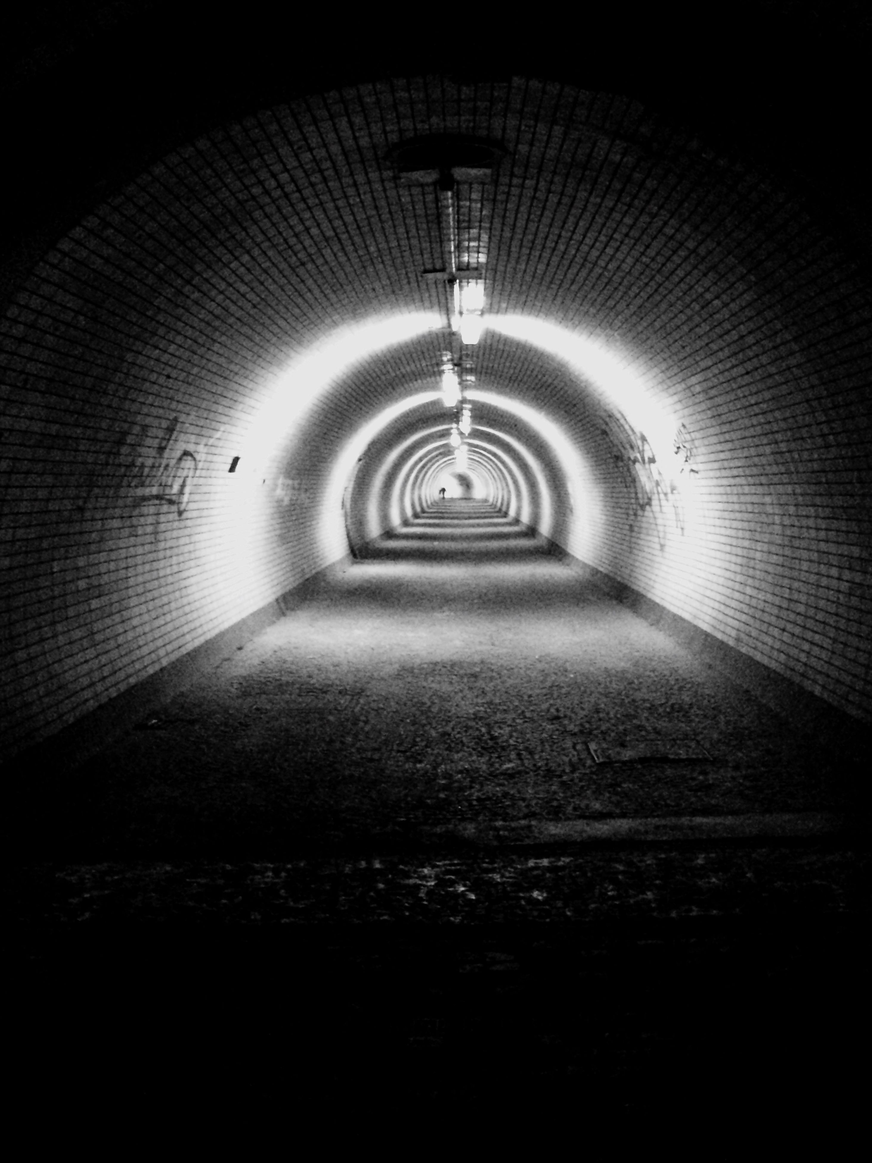 indoors, the way forward, illuminated, tunnel, diminishing perspective, lighting equipment, ceiling, vanishing point, arch, architecture, built structure, empty, electric light, wall - building feature, light - natural phenomenon, corridor, night, dark, no people, light at the end of the tunnel