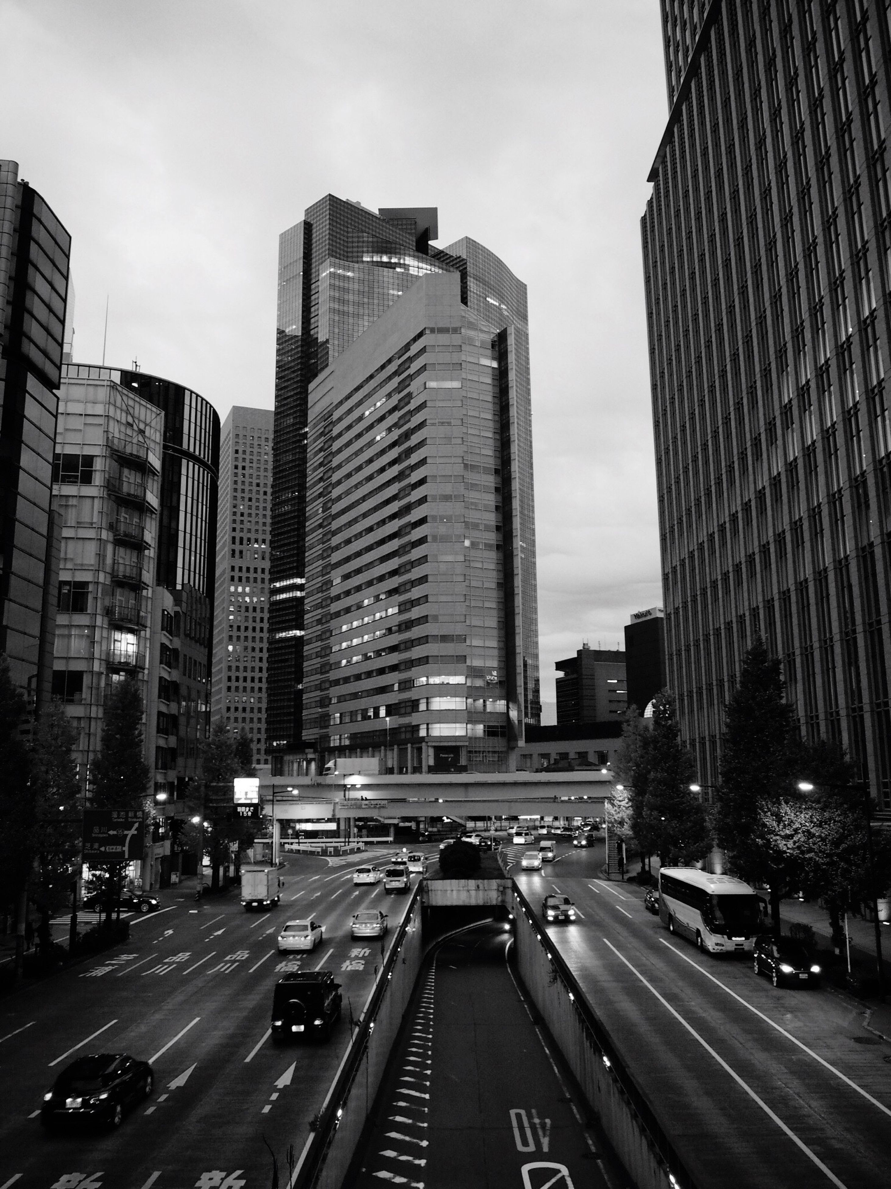 transportation, architecture, car, building exterior, city, built structure, road, land vehicle, mode of transport, street, road marking, the way forward, sky, city life, traffic, skyscraper, city street, diminishing perspective, on the move, modern