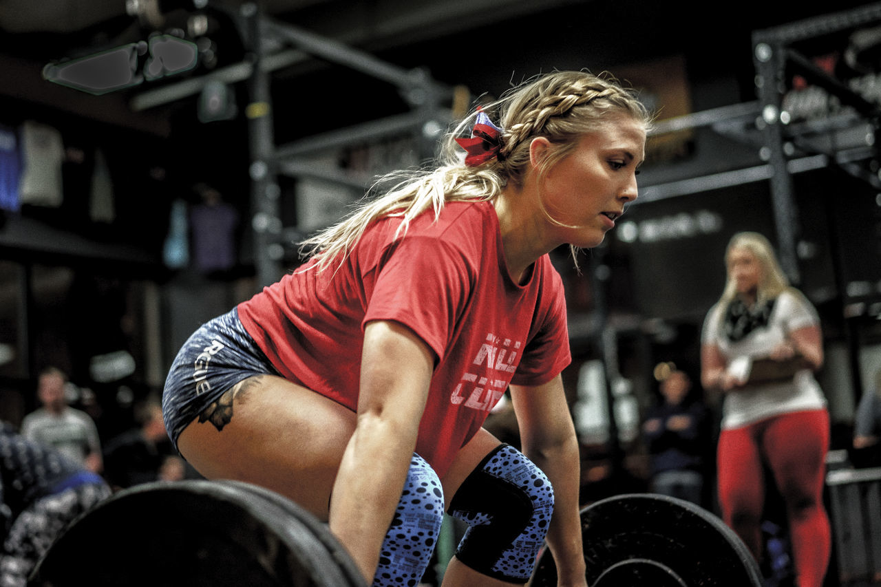 real people, blond hair, incidental people, lifestyles, focus on foreground, strength, sports training, sports clothing, indoors, gym, young adult, sport, leisure activity, young women, one person, exercise equipment, athlete, day, stadium, sportsman, boxing ring, adult, people