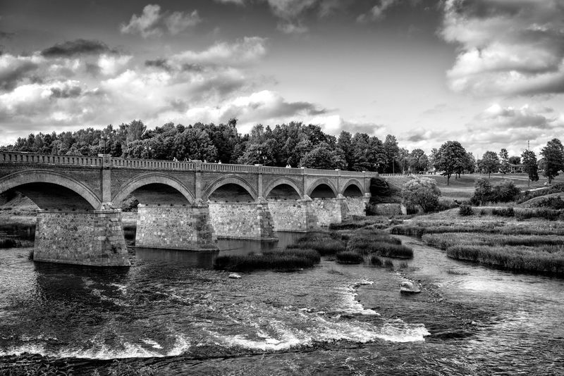 Old bridge with arches over the river. Arch Architecture Bridge - Man Made Structure Built Structure Cloud - Sky Connection Day Growth Kuldiga Latvia Motion Nature No People Outdoors River Sky Tree Water