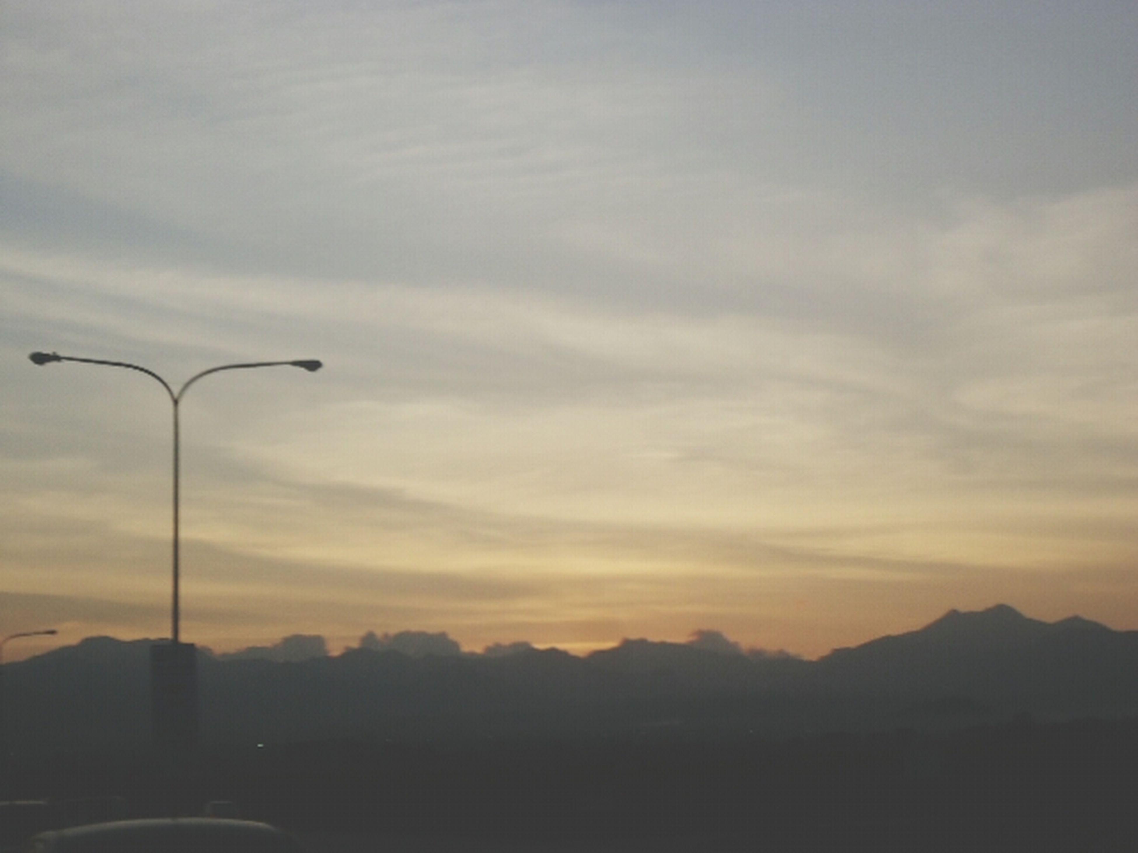 mountain, sky, sunset, street light, cloud - sky, scenics, silhouette, tranquility, mountain range, beauty in nature, tranquil scene, transportation, nature, lighting equipment, landscape, cloud, dusk, road, outdoors, idyllic