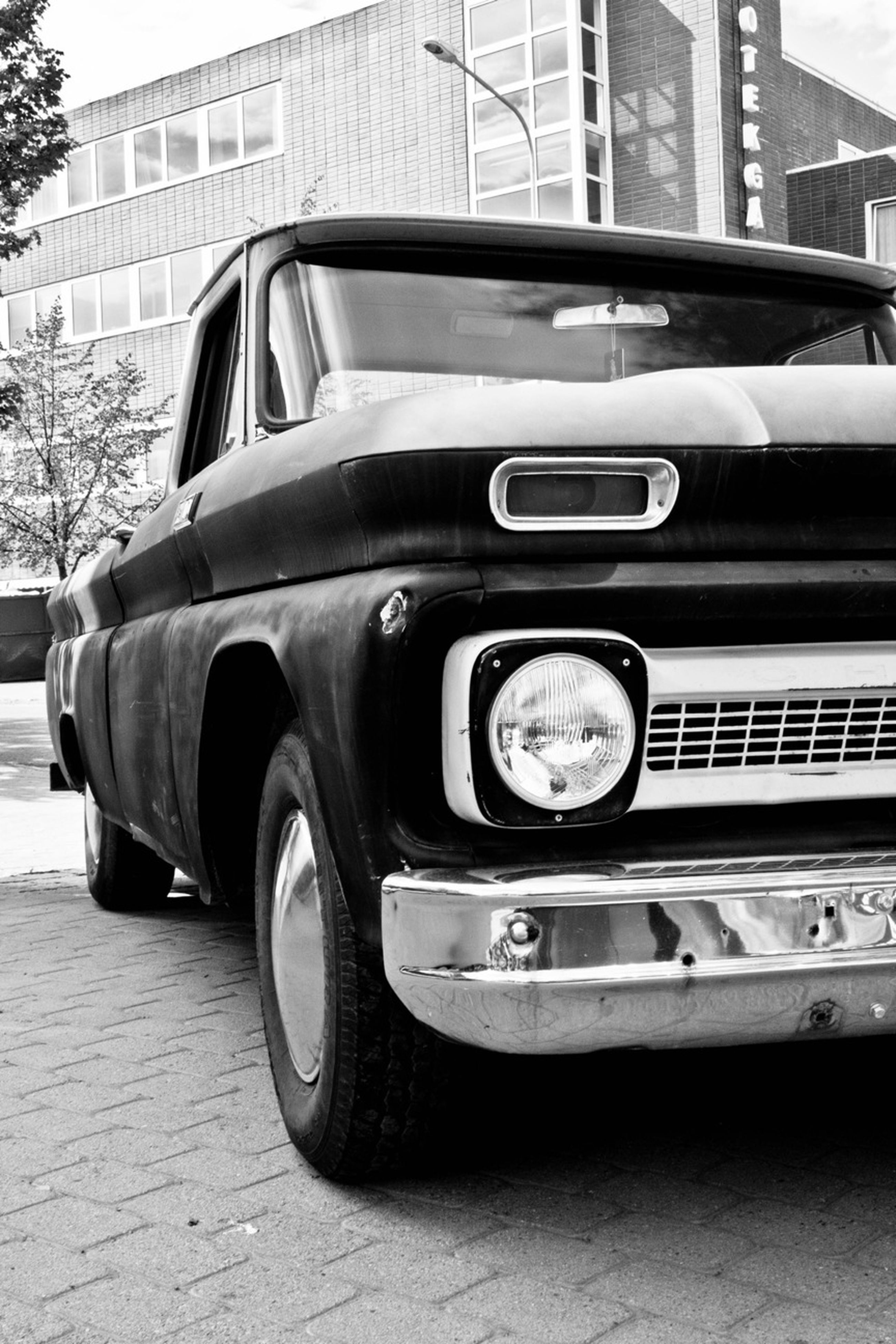 transportation, mode of transport, land vehicle, car, building exterior, architecture, built structure, street, travel, vintage car, stationary, city, road, vehicle, day, on the move, outdoors, bus, headlight, no people