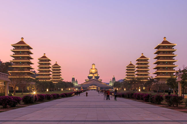 Kaohsiung, Taiwan - December 15, 2014: Sunset at Fo Guang Shan buddist temple of Kaohsiung, Taiwan with many tourists walking by. Architecture ASIA Asian  Asian Culture Buddha Buddha Statue Building Exterior Built Structure Capital Cities  City City Life Day Diminishing Perspective Façade Fo Guang Shan Kaohsiung Outdoors Religion Sky Summer Taiwan The Way Forward Tourism Tradition Travel Destinations