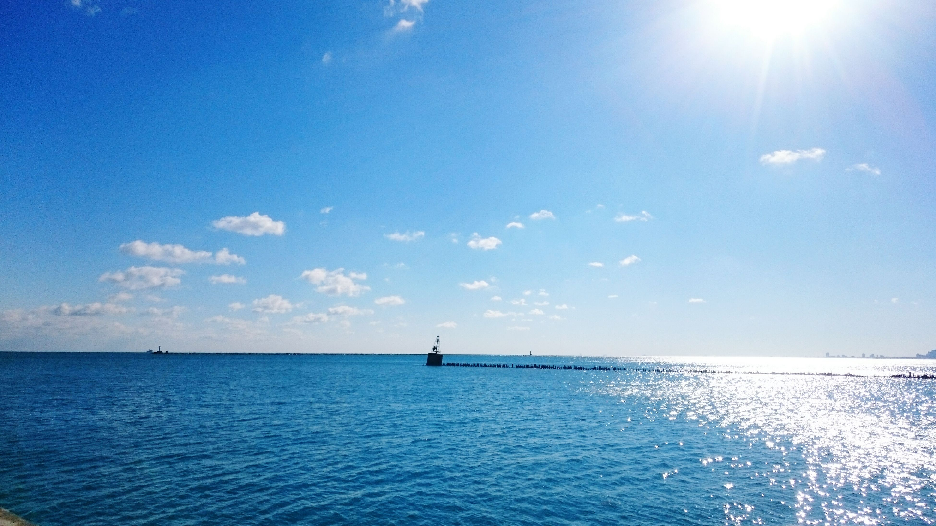 sea, water, horizon over water, blue, waterfront, tranquility, tranquil scene, sky, scenics, beauty in nature, sun, sunlight, sunbeam, nature, rippled, nautical vessel, idyllic, seascape, transportation, day