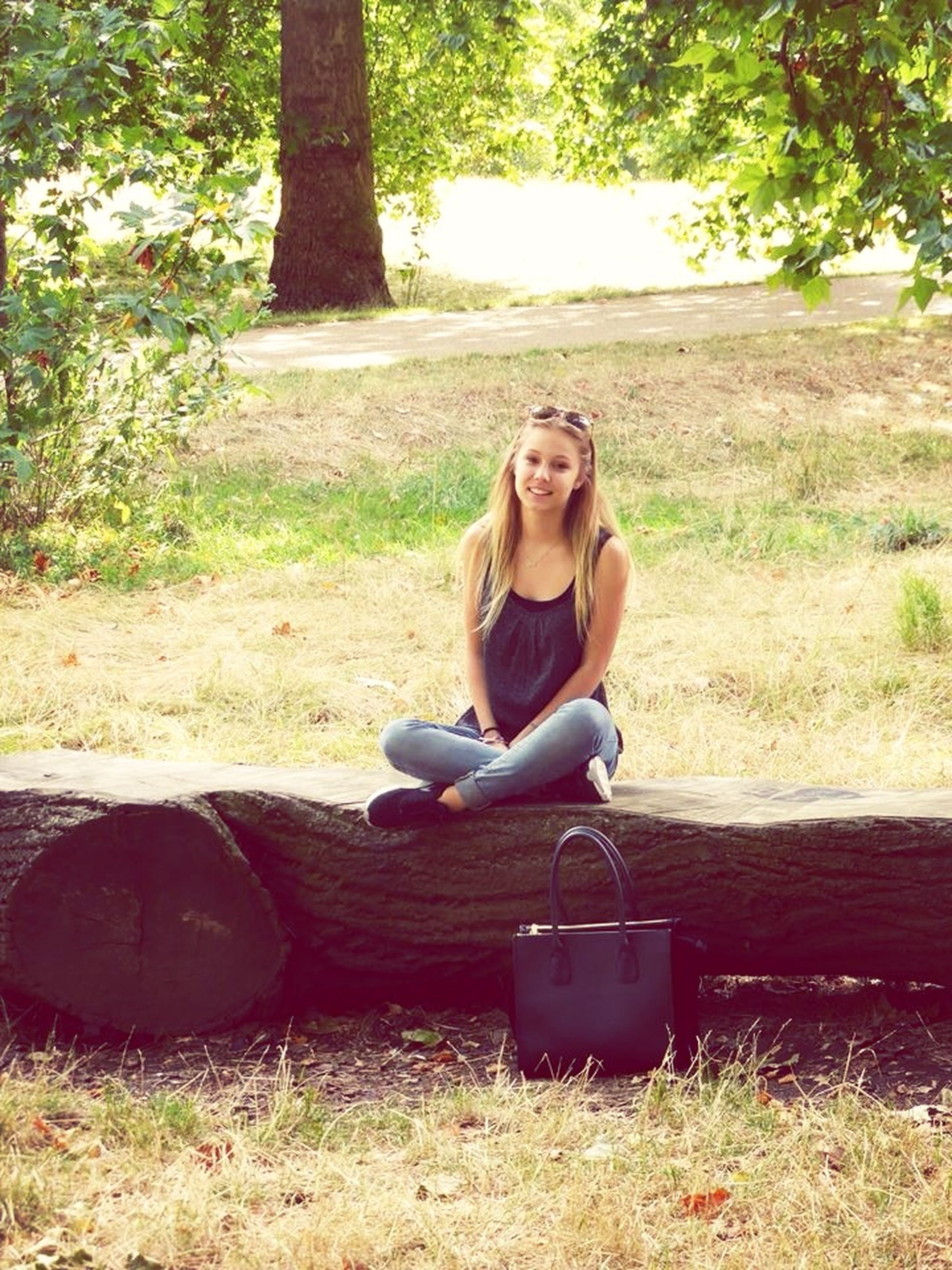 person, sitting, young adult, looking at camera, portrait, casual clothing, lifestyles, leisure activity, smiling, tree, front view, relaxation, happiness, young women, full length, sunglasses, park - man made space
