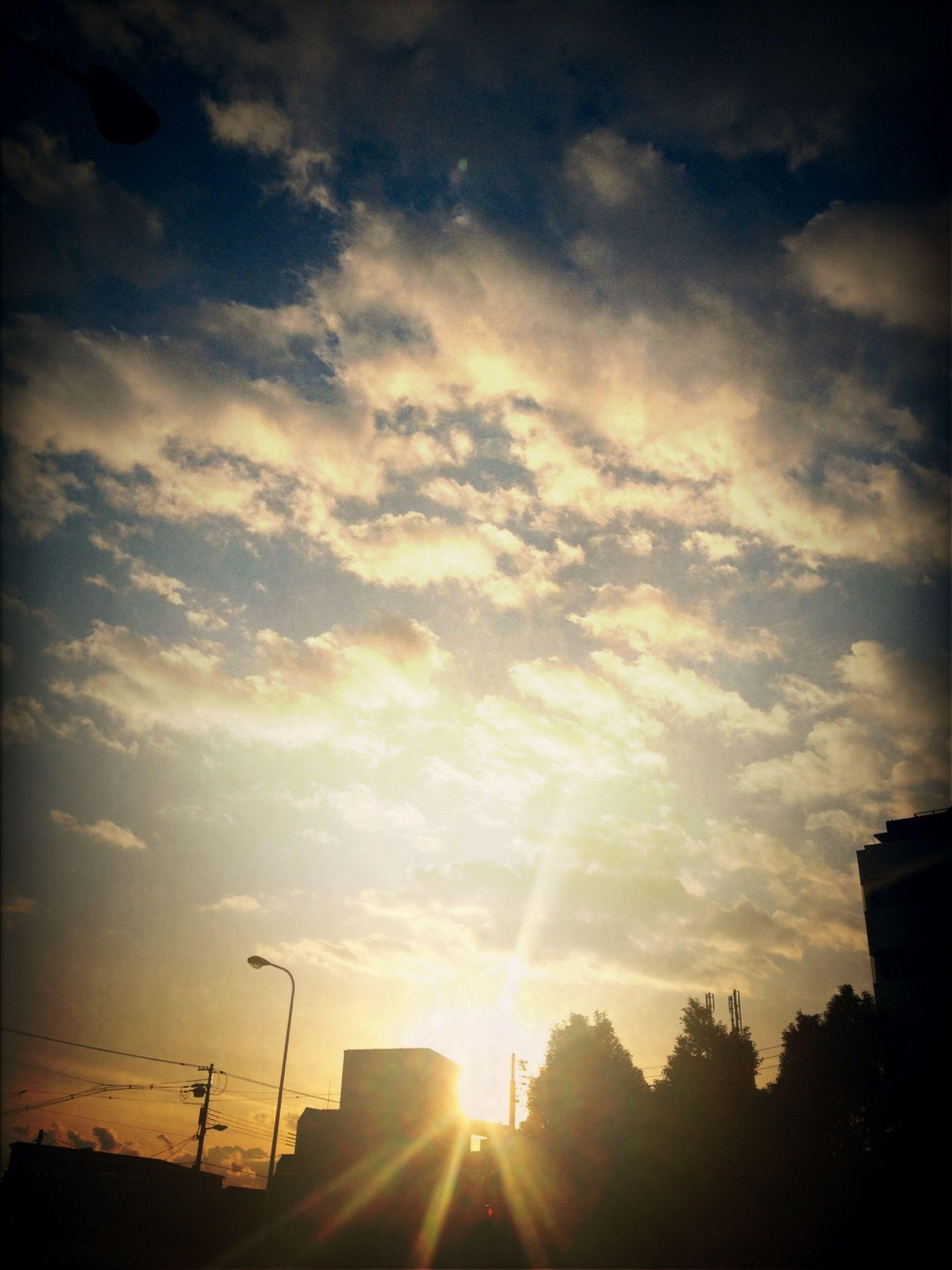 sun, sunset, sunbeam, sky, silhouette, sunlight, cloud - sky, lens flare, low angle view, built structure, architecture, building exterior, beauty in nature, nature, cloud, back lit, orange color, scenics, tree, outdoors