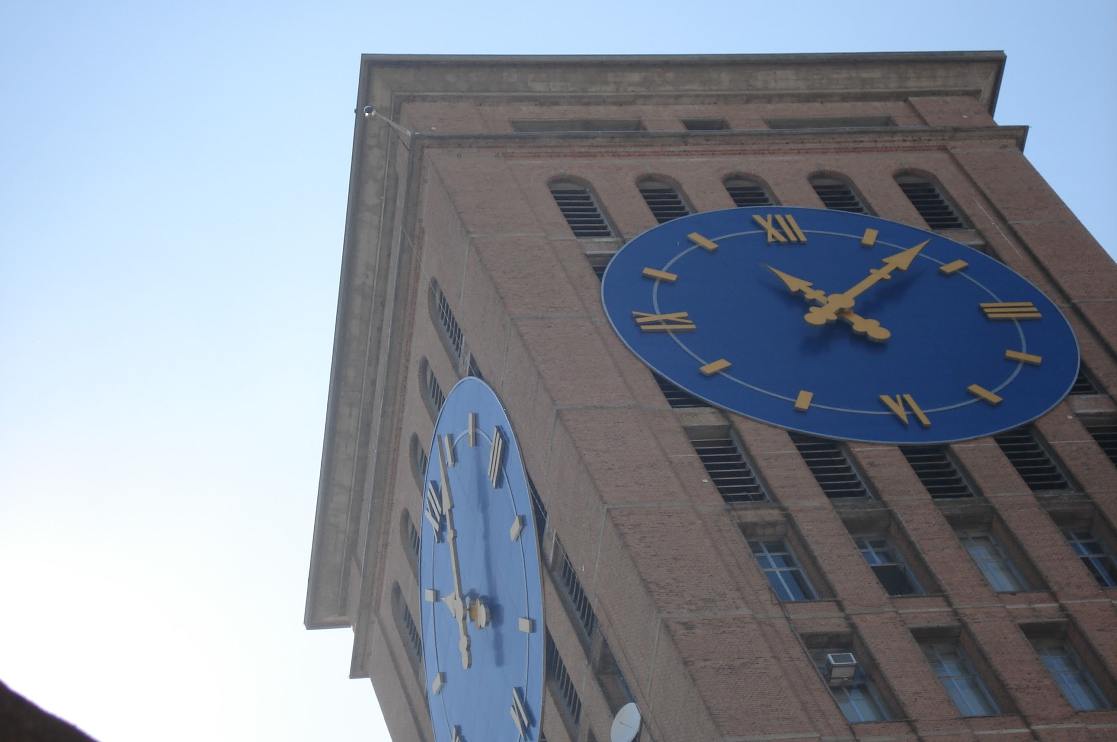 low angle view, architecture, built structure, building exterior, clock, clear sky, time, clock tower, text, communication, western script, day, outdoors, clock face, city, no people, circle, tower, sky, history