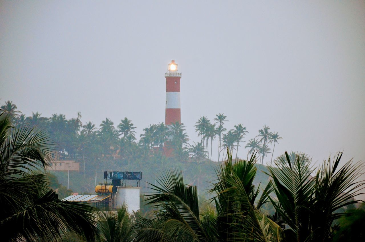 lighthouse, guidance, architecture, building exterior, direction, tower, built structure, safety, protection, tree, day, palm tree, growth, outdoors, no people, clear sky, nature, sky